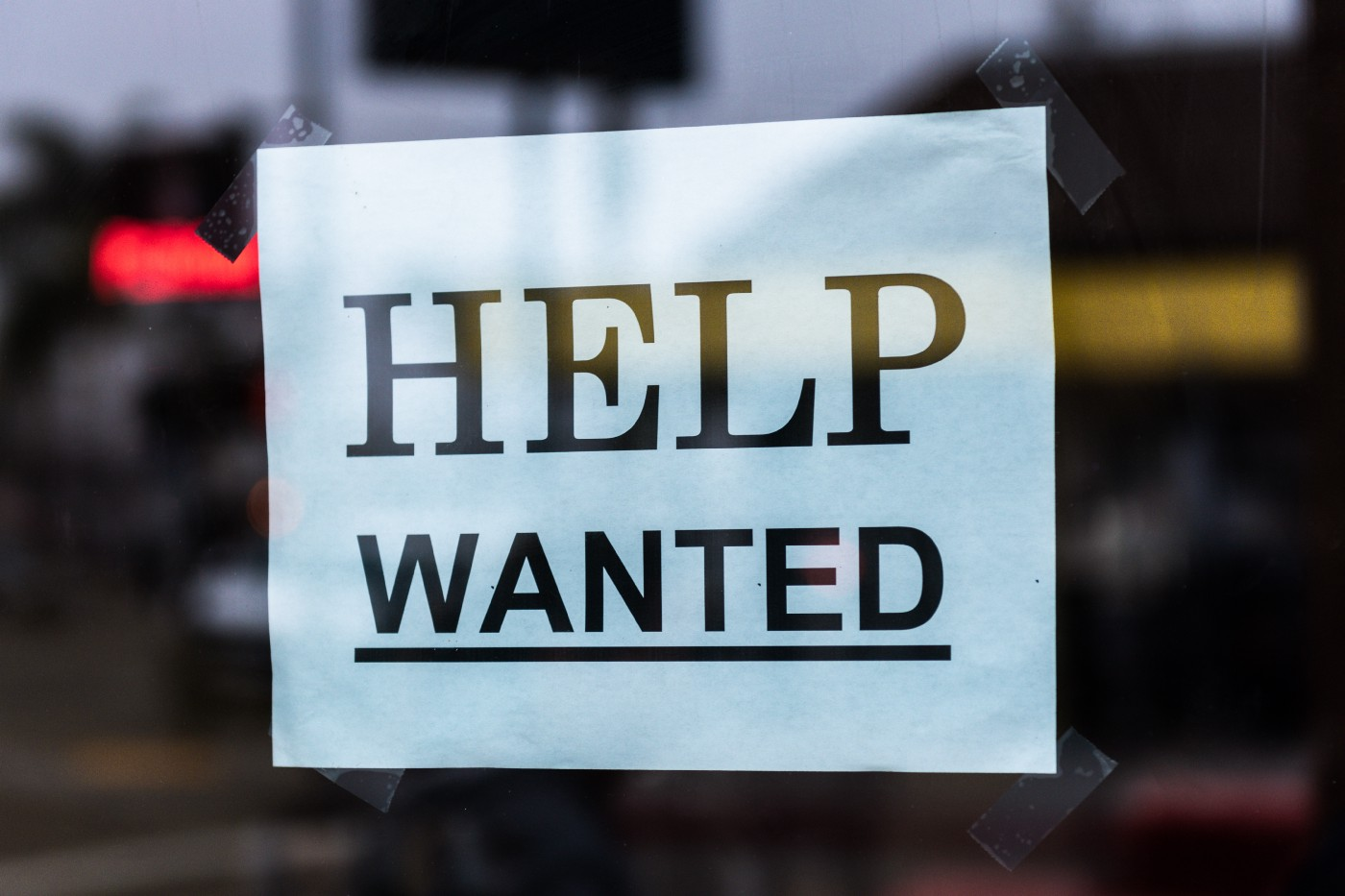 Help Wanted printed sign stuck up in a window