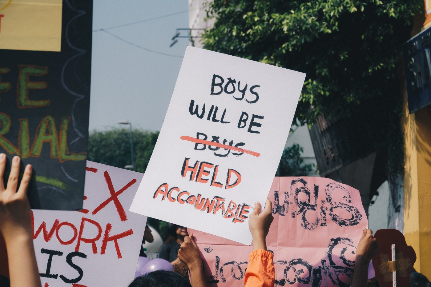 Protest with sign saying boys will be held accountable.