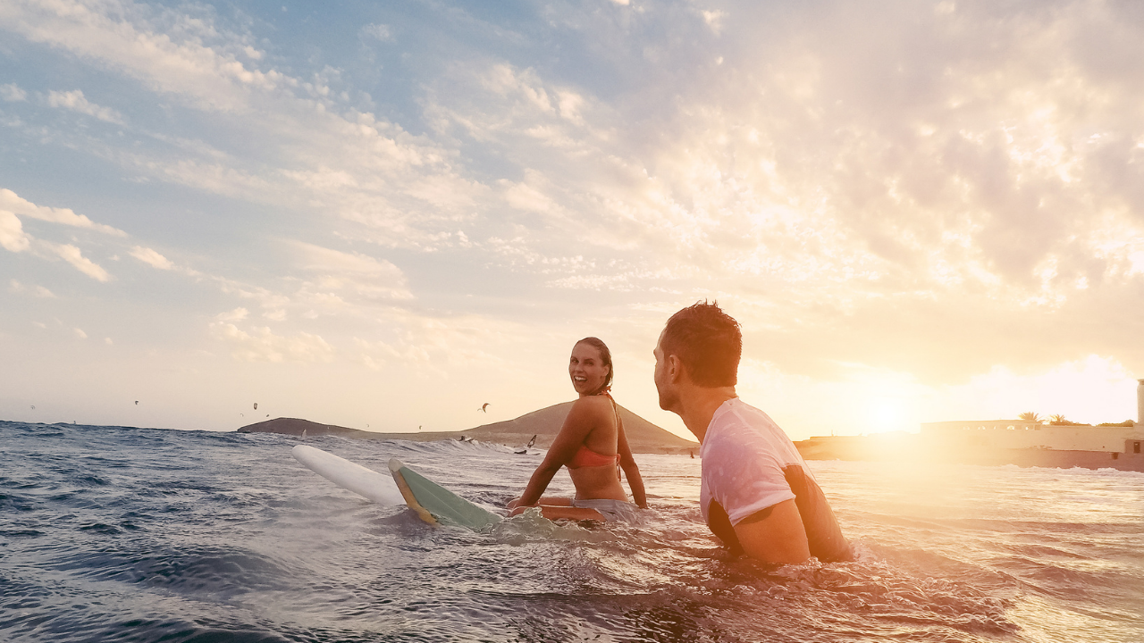 Woman and man surfing in ocean with warm sunlight