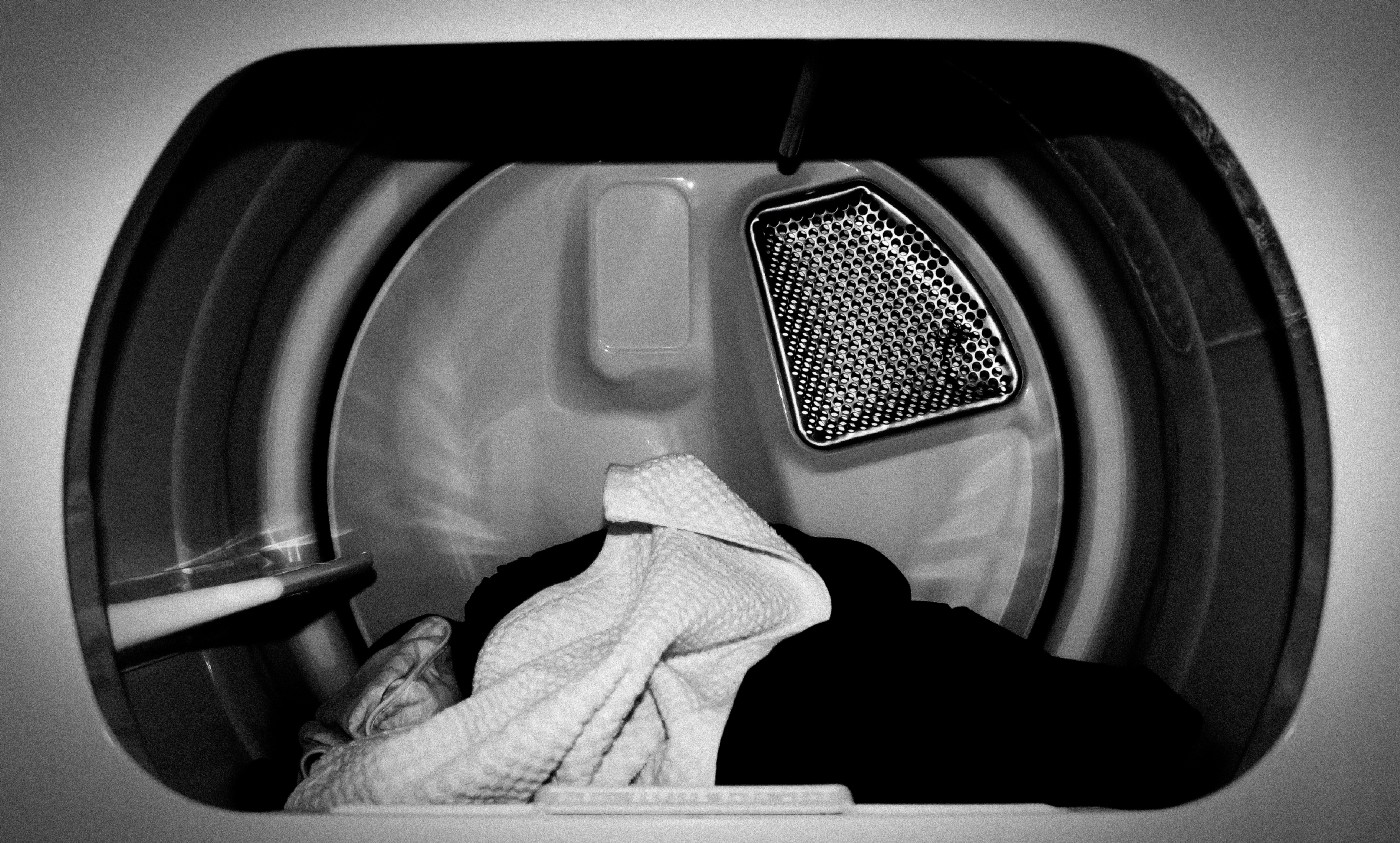 Black and white photo of laundry piled in a dryer.