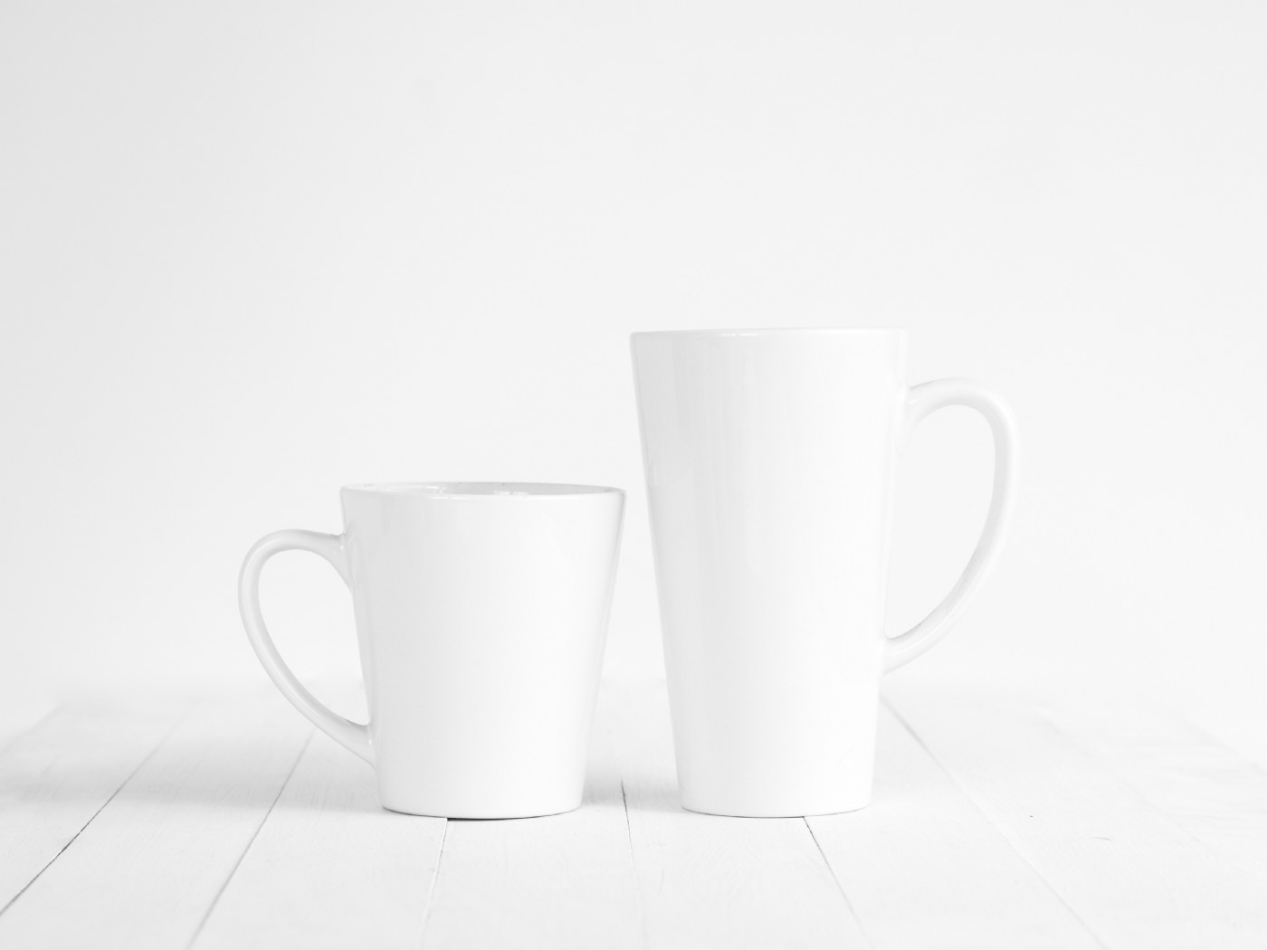Two white mugs standing side by side—one small, one tall