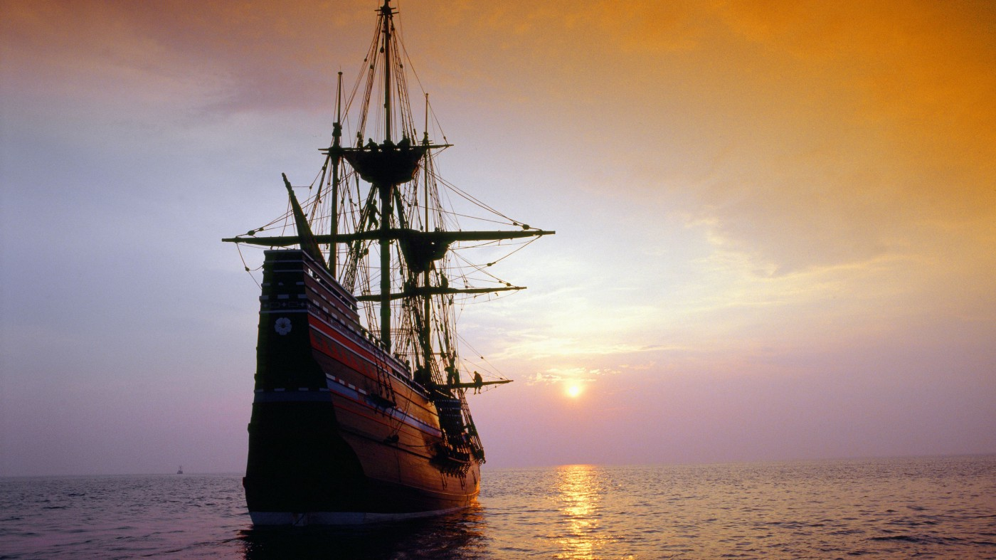 An old pirate ship sails into the sunset