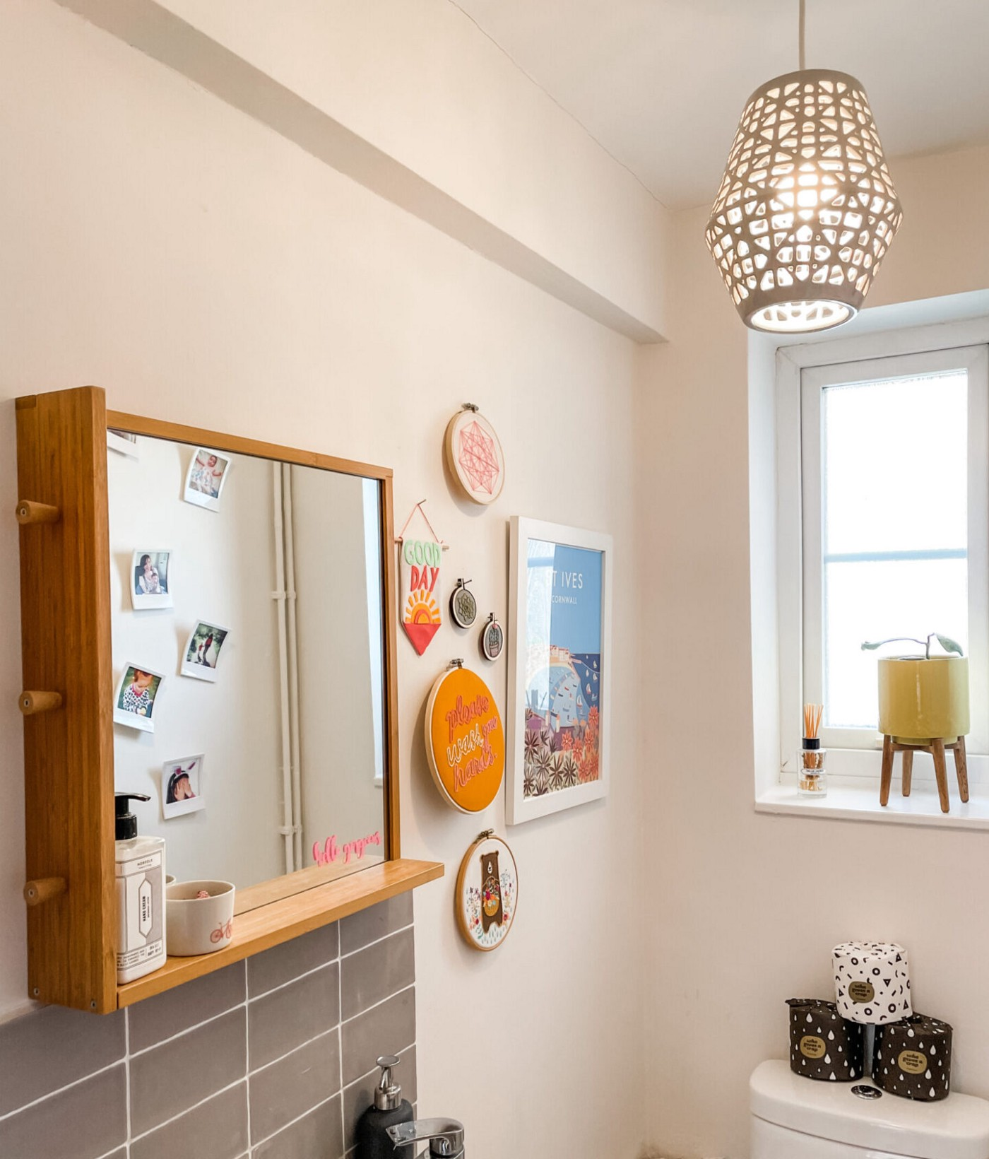 Cloakroom with a bamboo-framed mirror and shelf above a sink tile tiled with grey tiles, lit up by a new eco-friendly LED bulb in a grey shade. There is a collection of brightly coloured embroideries and a vintage-style art print of St Ives on the wall, and a window with a yellow plant stand on the windowsill