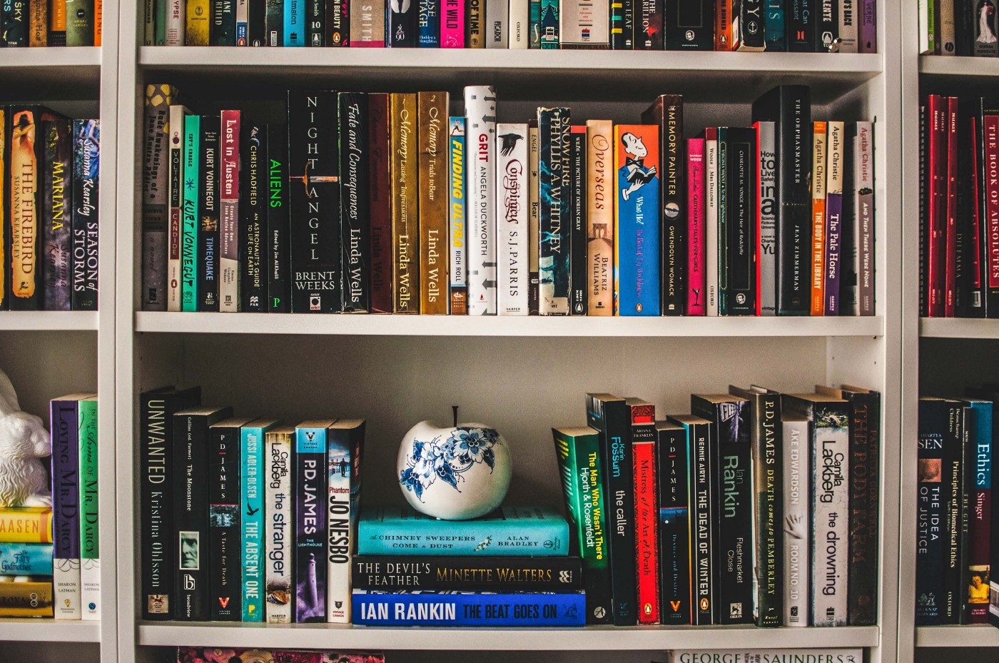 colorful bookshelf with ceramic bowl and lots of books