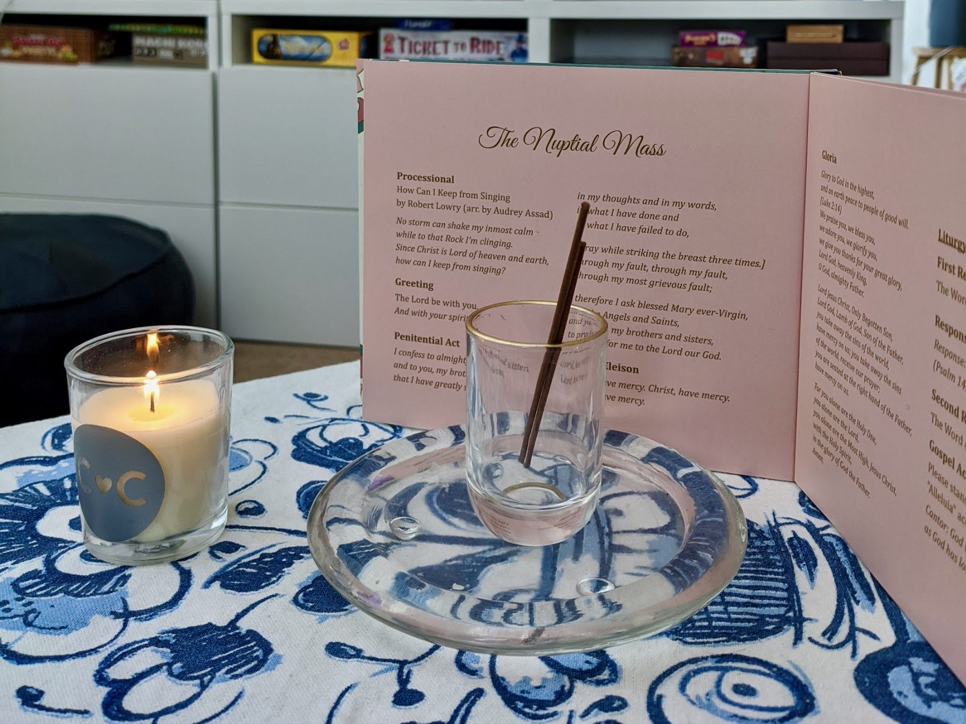 Incense, a candle, and a bound wedding program on a table with a blue and white floral tablecloth.