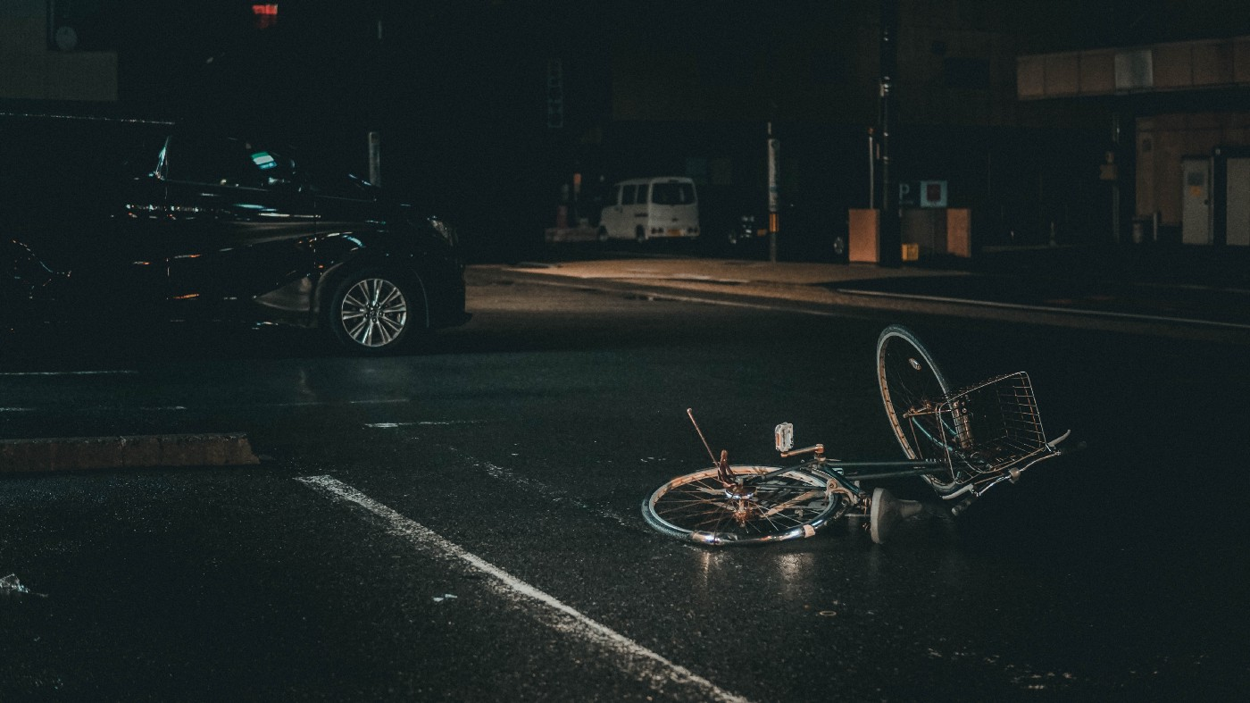 Image of bicycle on road at night, suggesting that the bicyclist may have fallen off.