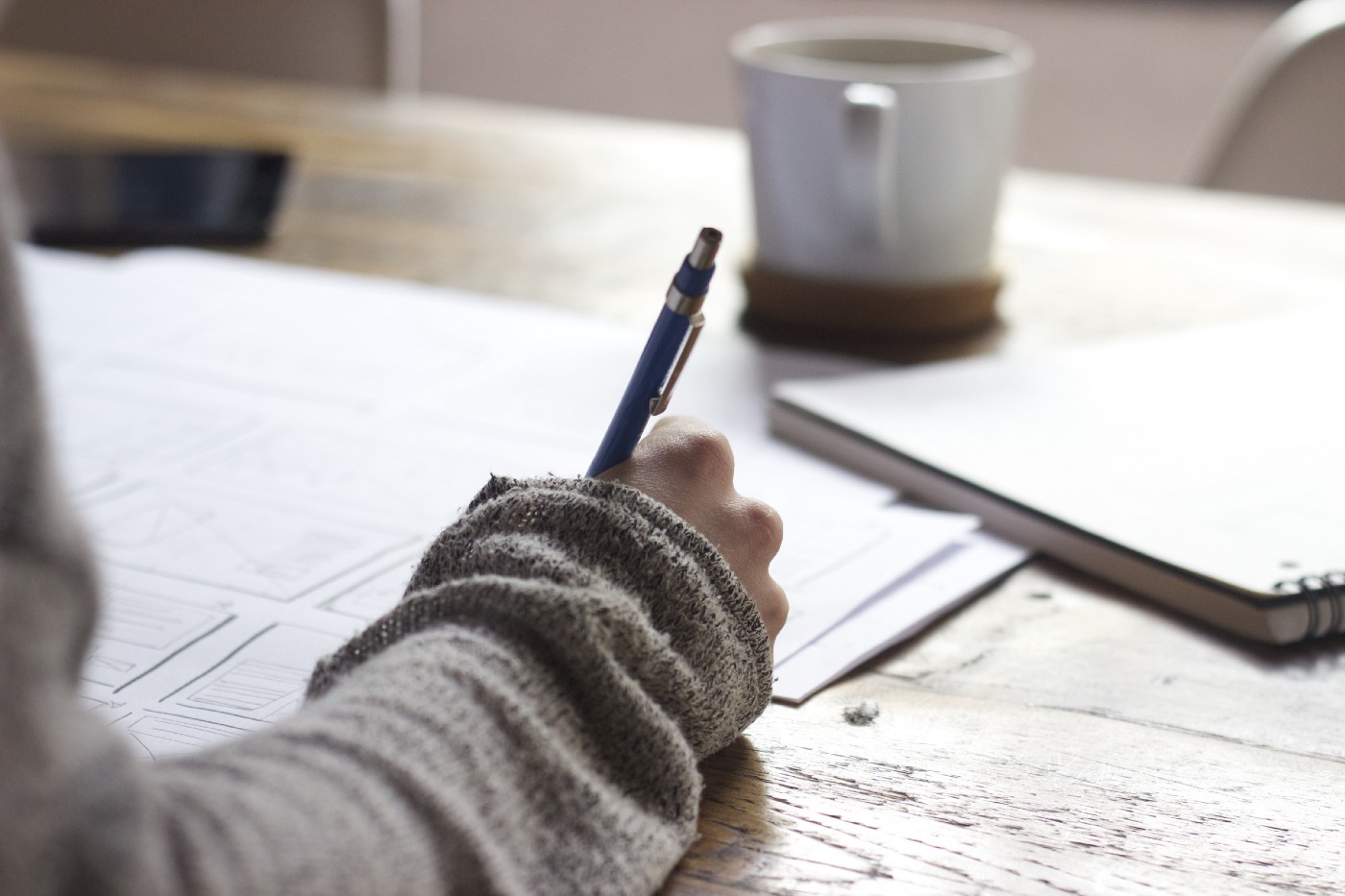 A person writes notes on freestanding papers next to a presumably full notebook. On the same table, a cup of espresso sits.