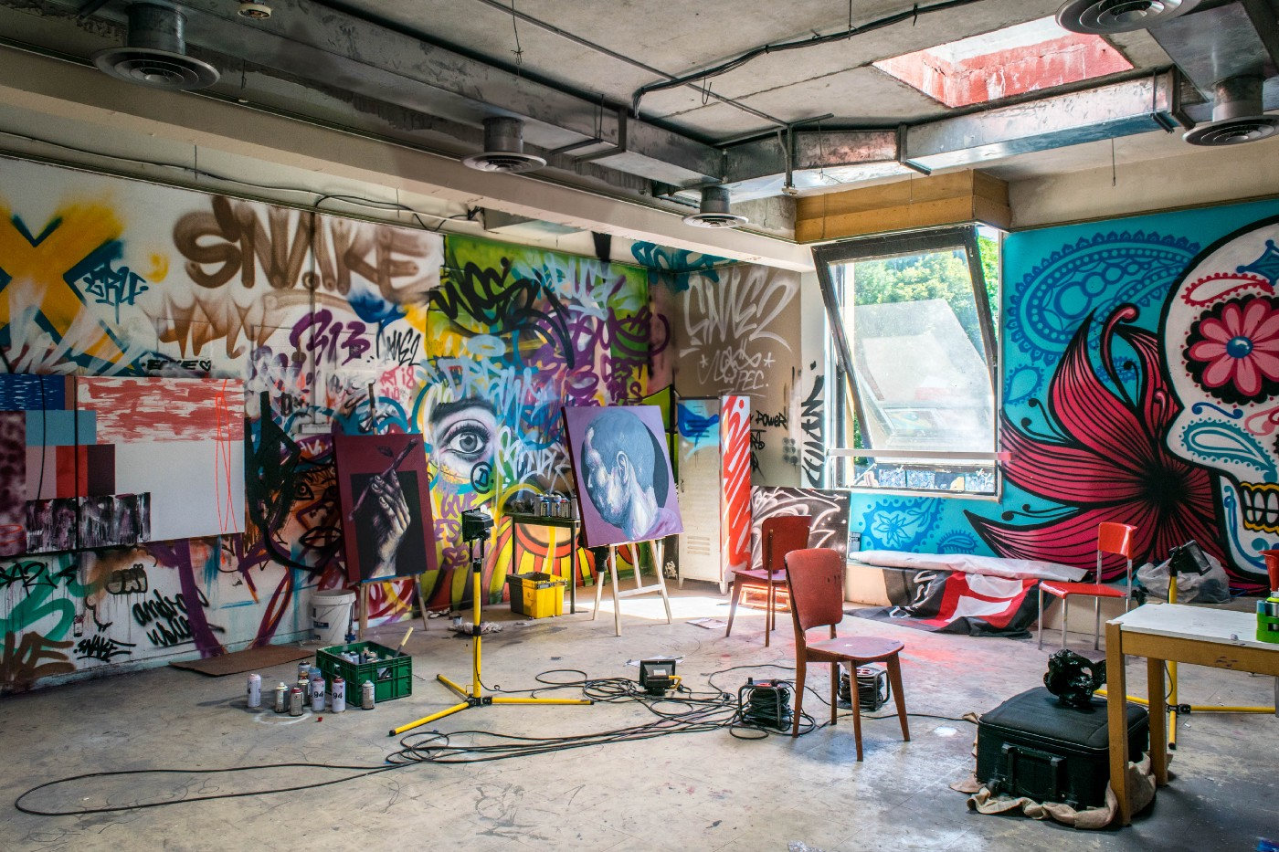 Somewhat messy painting studio with canvases, and painting on the wall like graffiti.