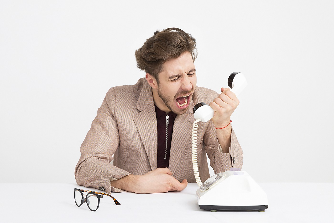 a person screaming into a telephone receiver. the telephone is lying on a surface in front of the person as are a pair of glasses