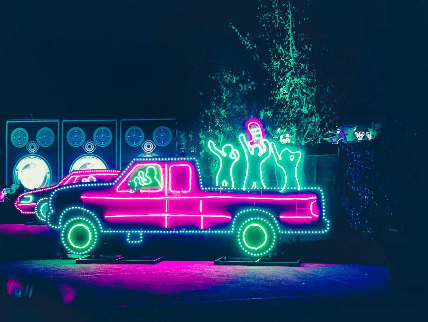 A neon sculpture in the form of a truck with people dancing in the back. Project Raven Novel by Jim Latham
