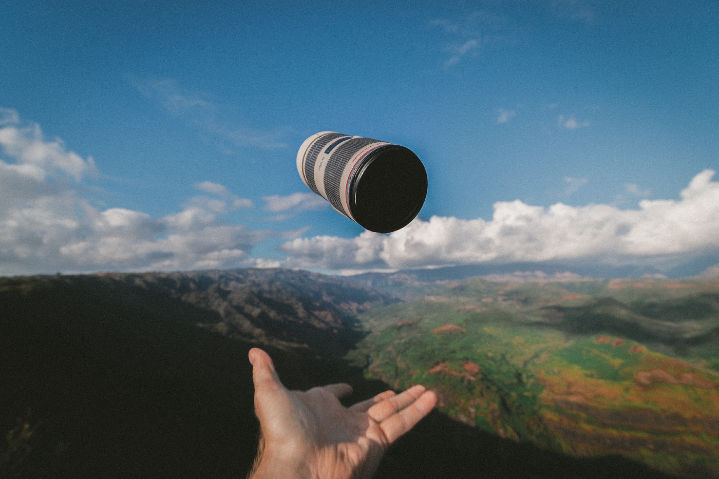 A hand throwing a cup into the air with a scenic background of mountains and grasslands.