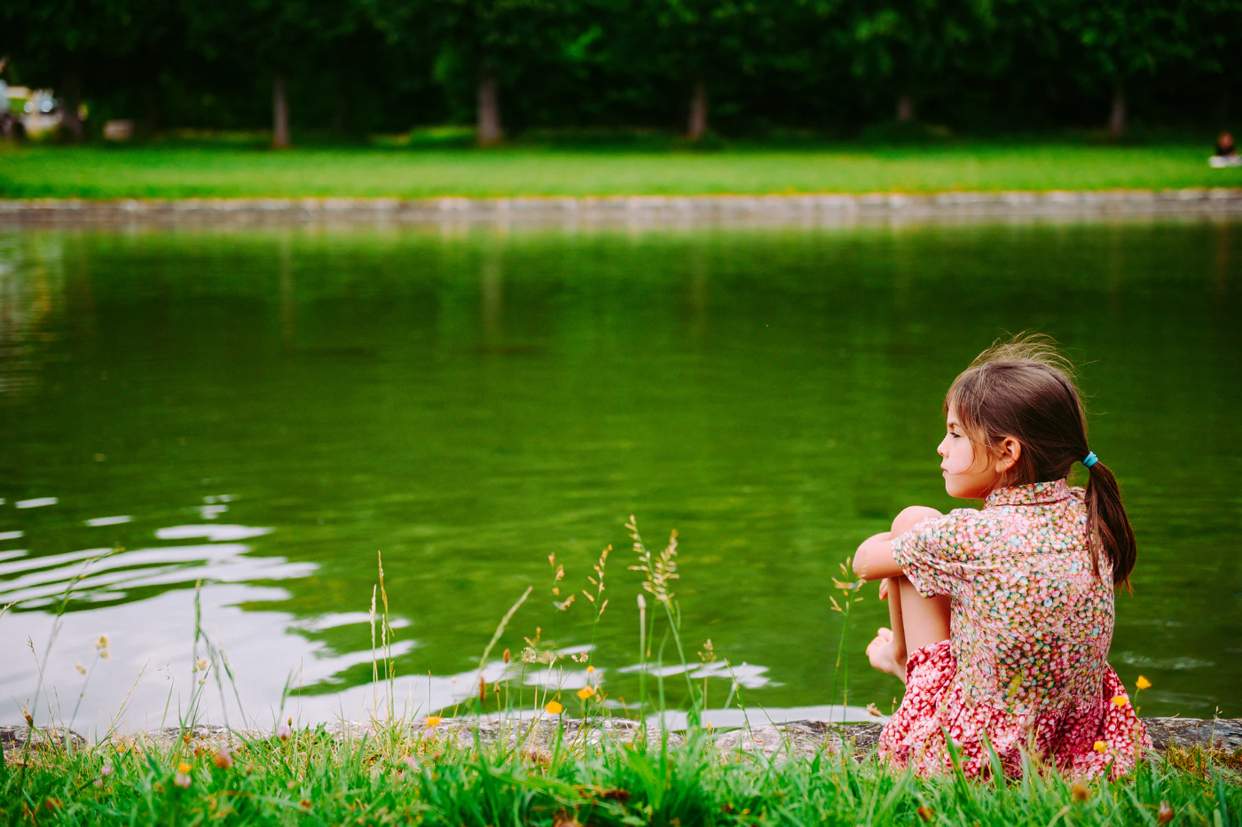 Young girl sitting in front of pond