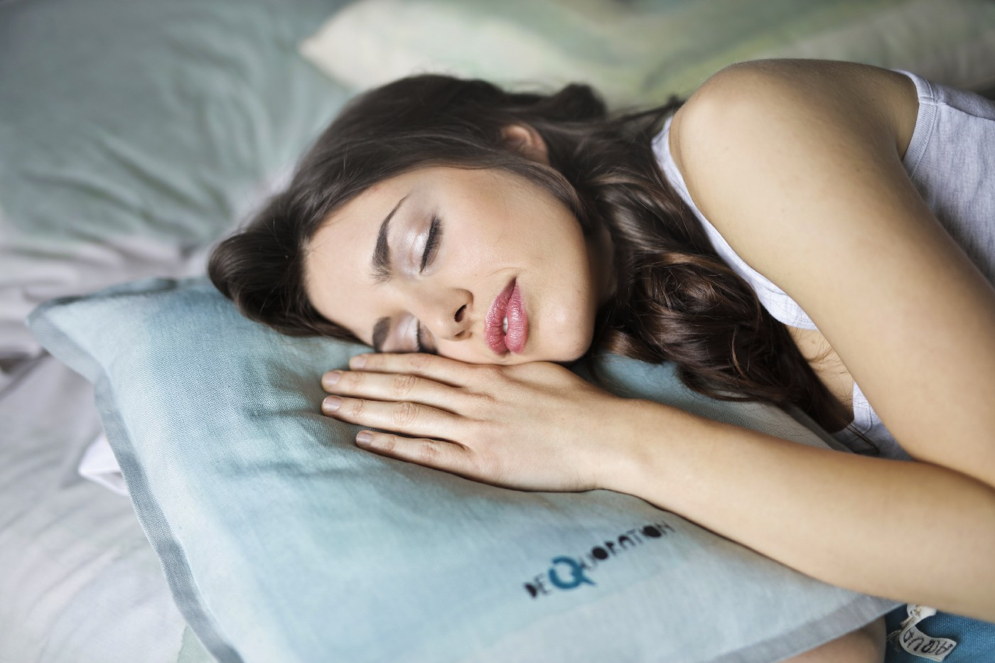 Woman sleeping while resting her head and hand on a pillow
