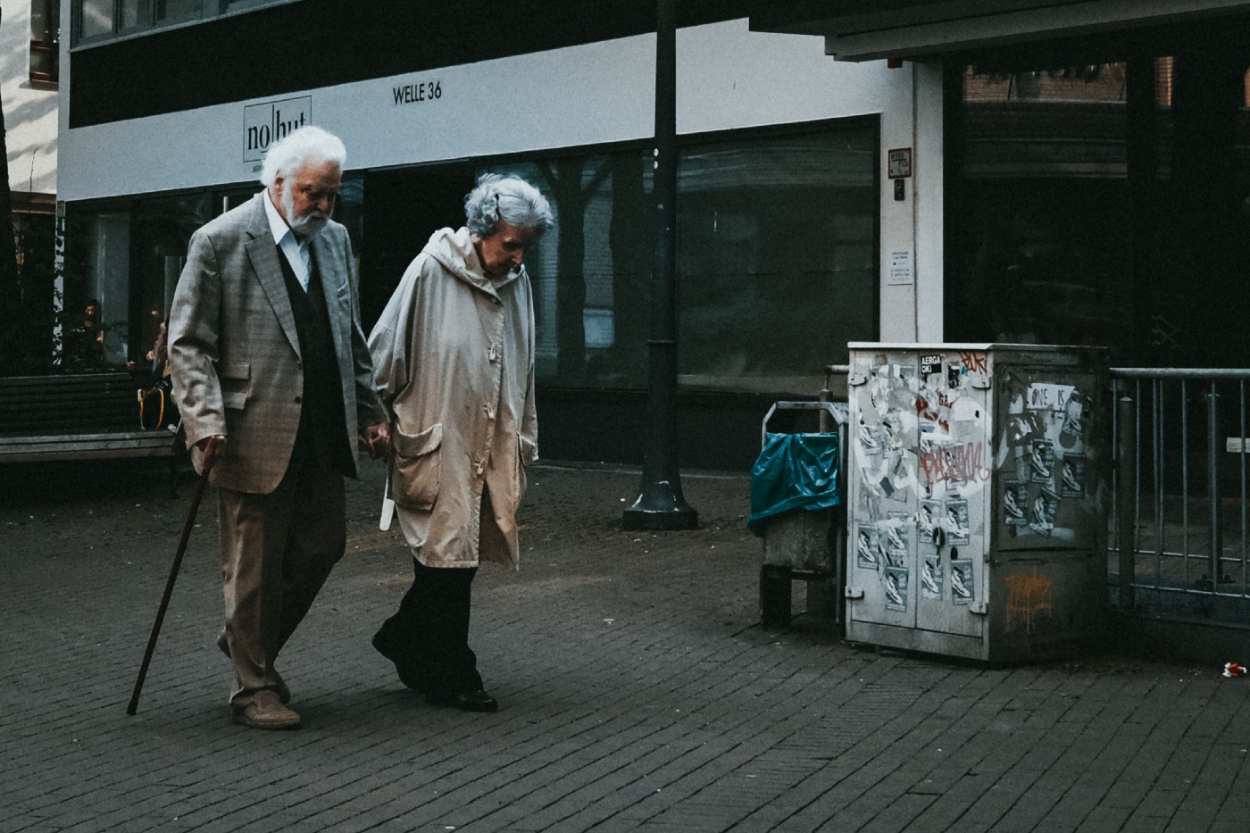 An elderly couple walk along a city street. They are both looking down. The man has a cane.