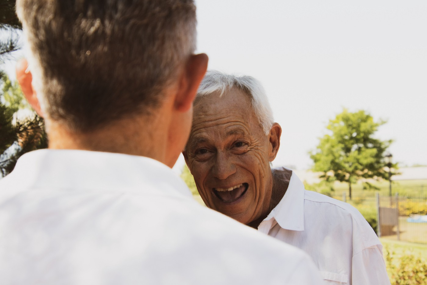 Younger man in foreground conversing with laughing older man