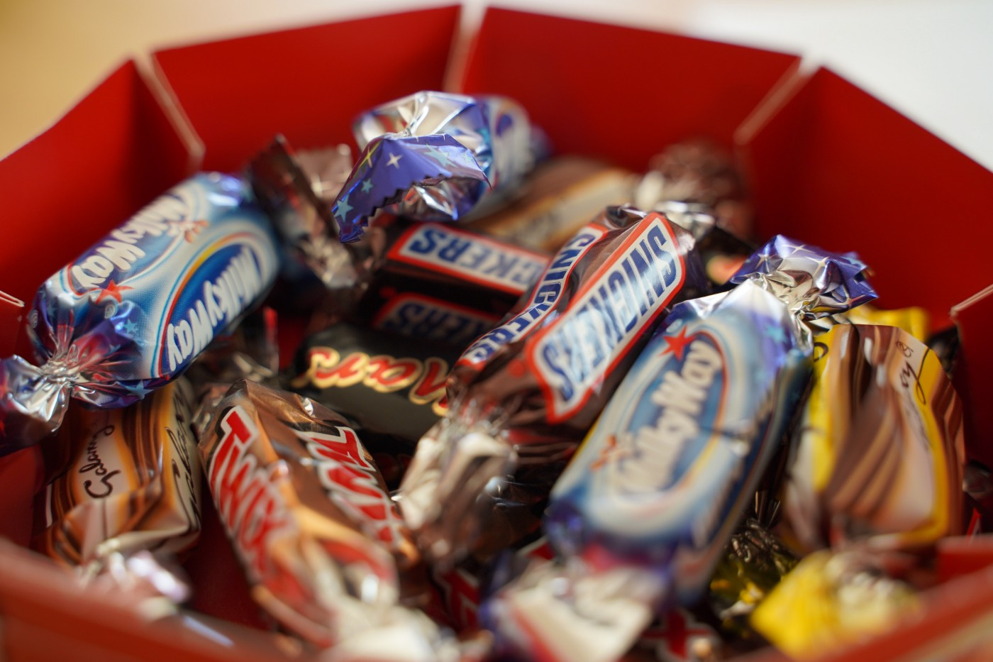 Bowl of mini candy bars with Snickers, Twix, and Milky Way in focus.