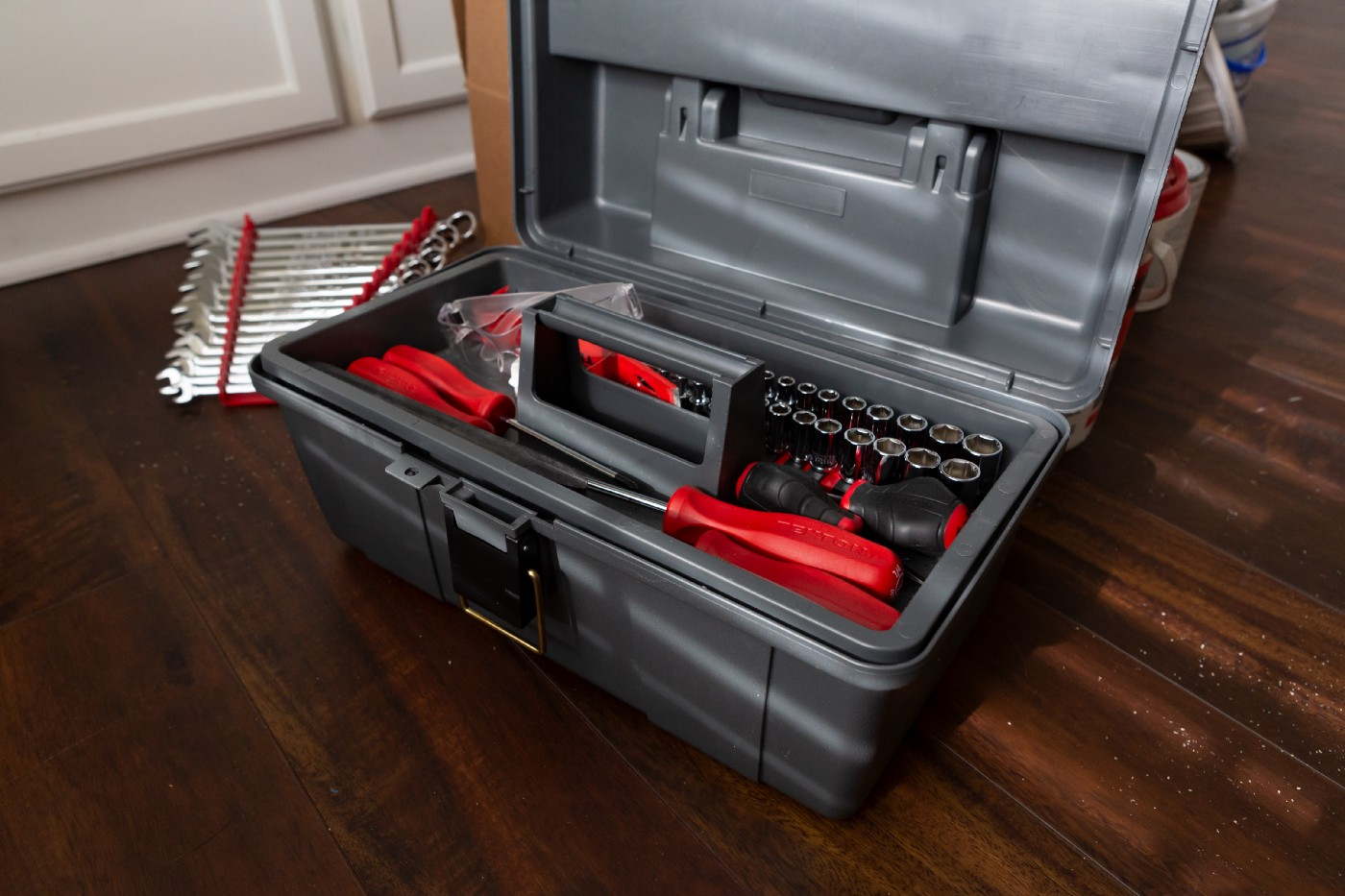 A neatly organized tool box on a dark wood floor.