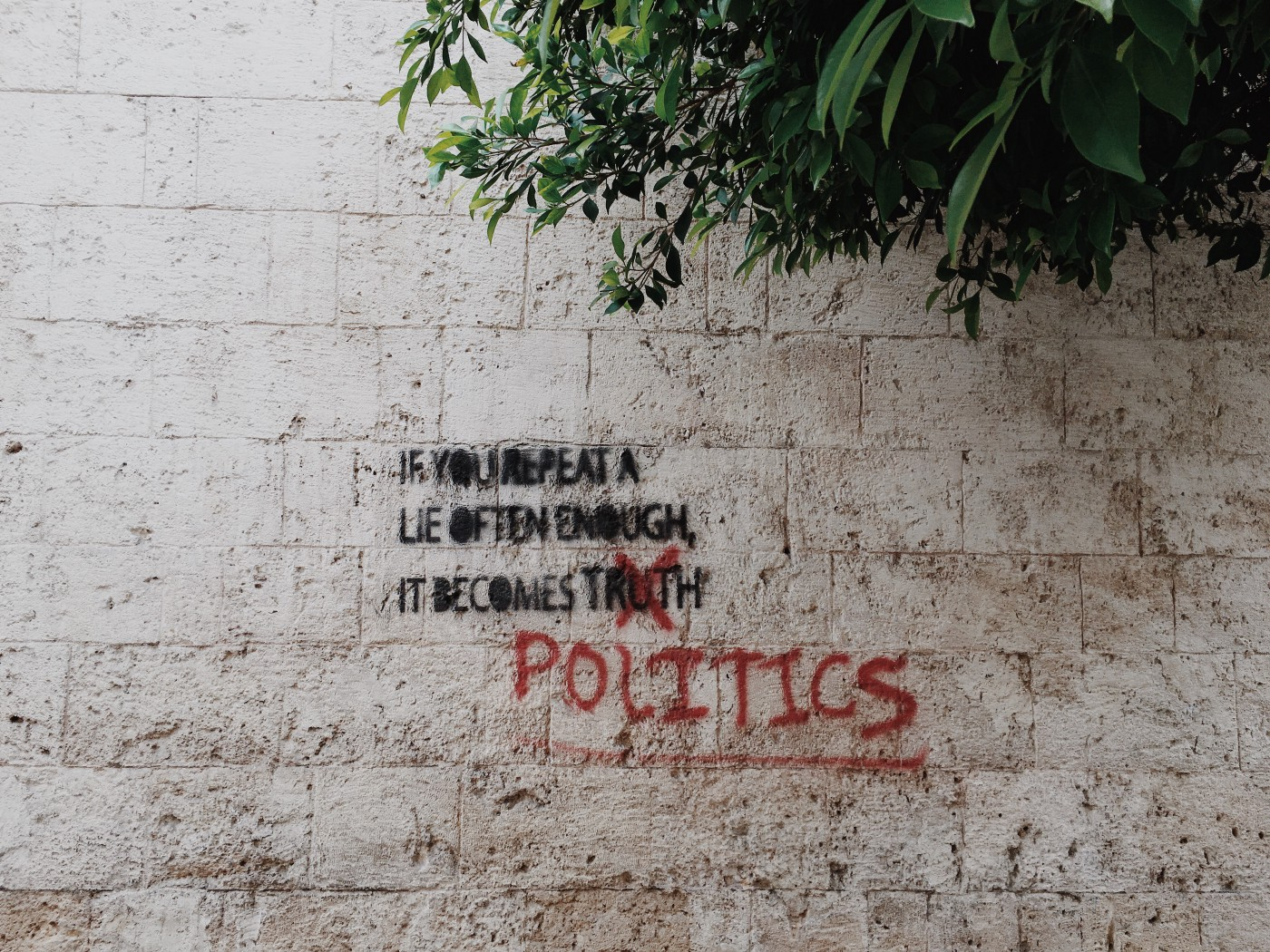 Graffiti quote on a wall saying: If you repeat a lie often enough, it becomes POLITICS.