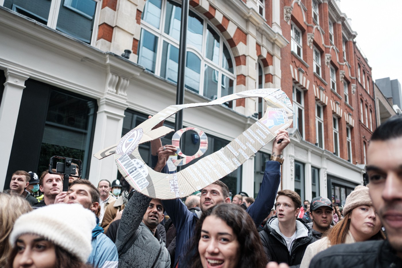 Protestors march carrying the symbols of the QAnon conspiracy group.