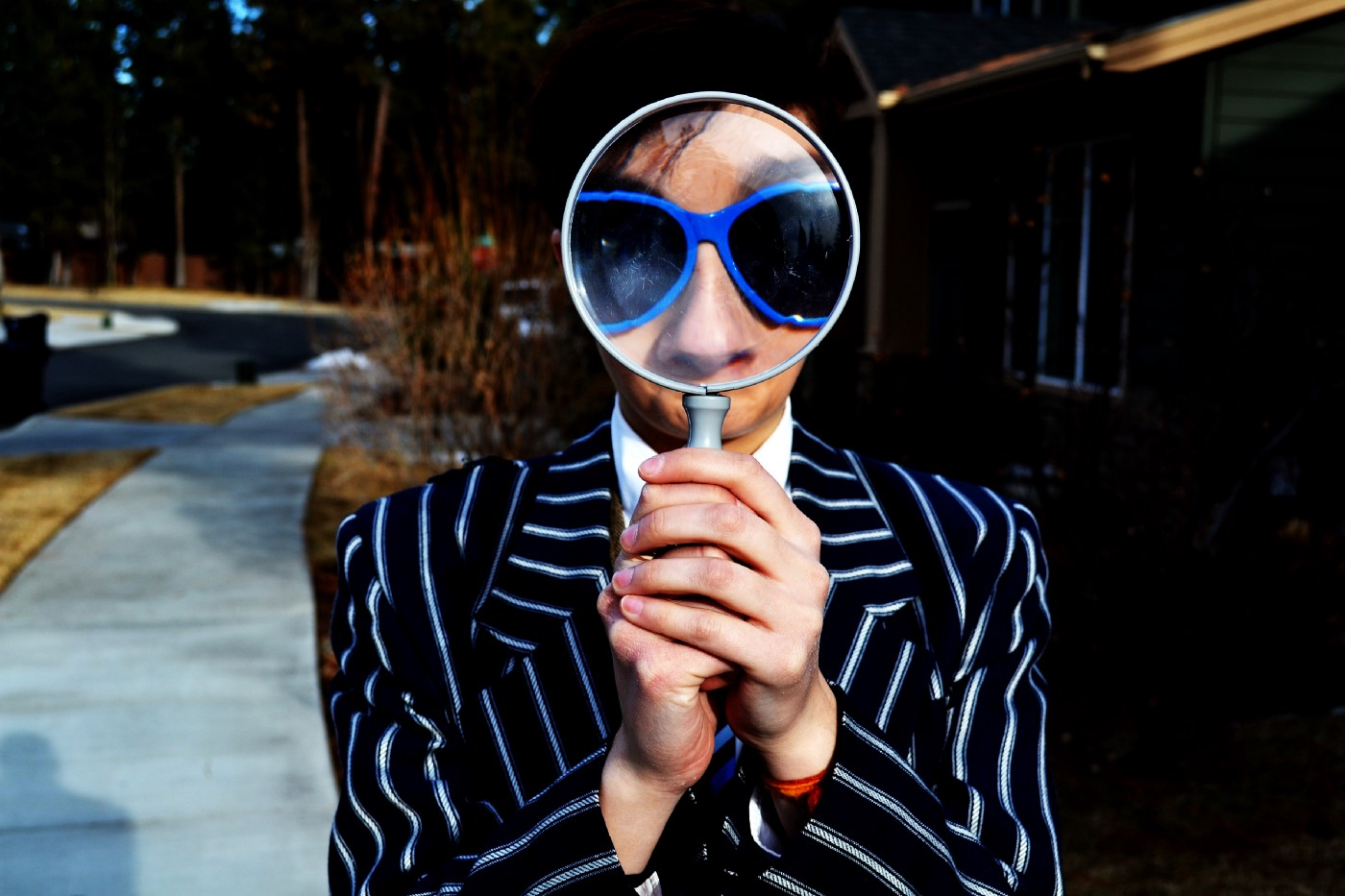 A person who is wearing black suit and black spectacle cornered with blue colour, holding a magnifier lens from both hands.