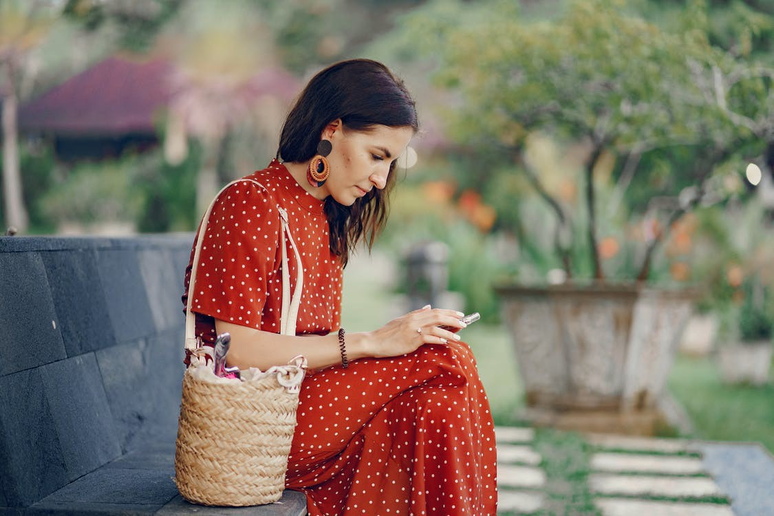 woman sitting on bench looking at her phone