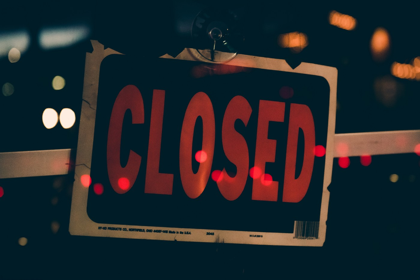 "A ""closed"" sign with red letters on a black background."