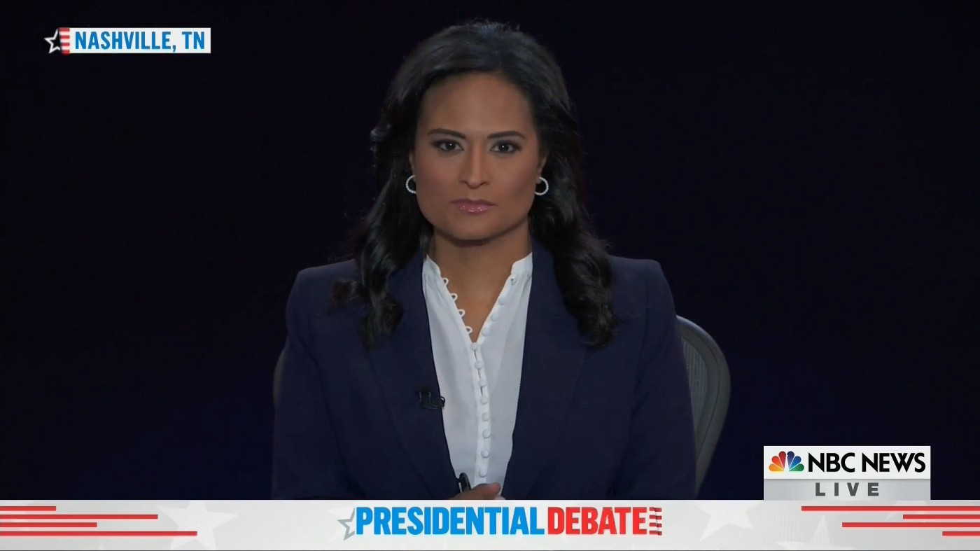 Screenshot of Kristen Welker, moderator, wearing a white shirt, navy blue sports jacket, earrings, and hair curls.