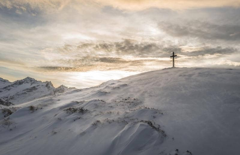 Christian Cross on top of a snow covered mountain