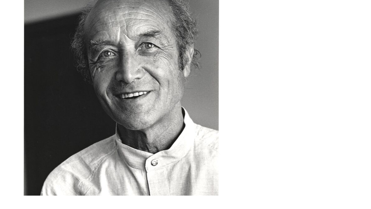 Black and white photo of Isamu Noguchi looking alive and happy in a light mandarin collar shirt. Photo by Mimi Jacobs.