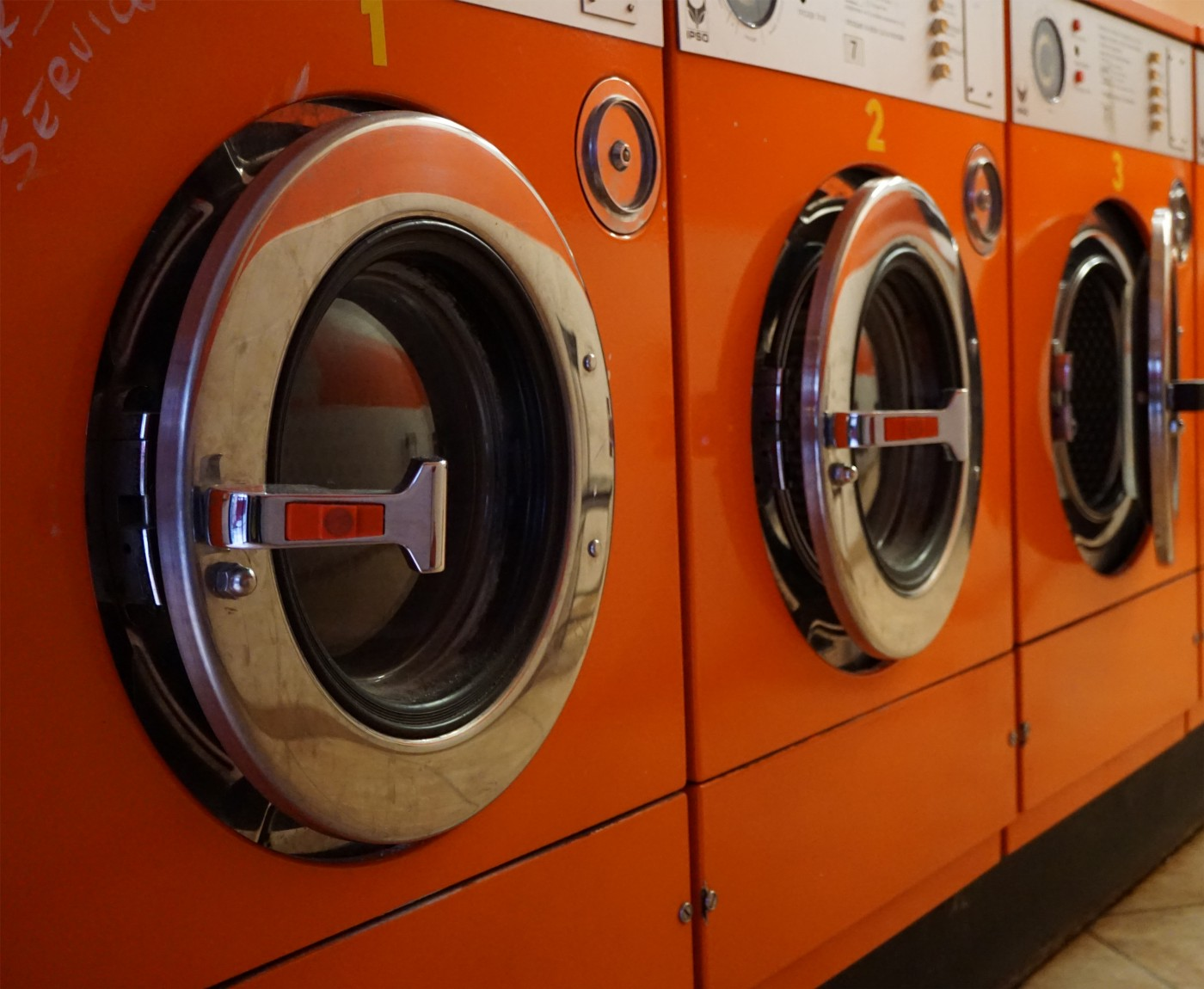 Three washing machines in a laundry