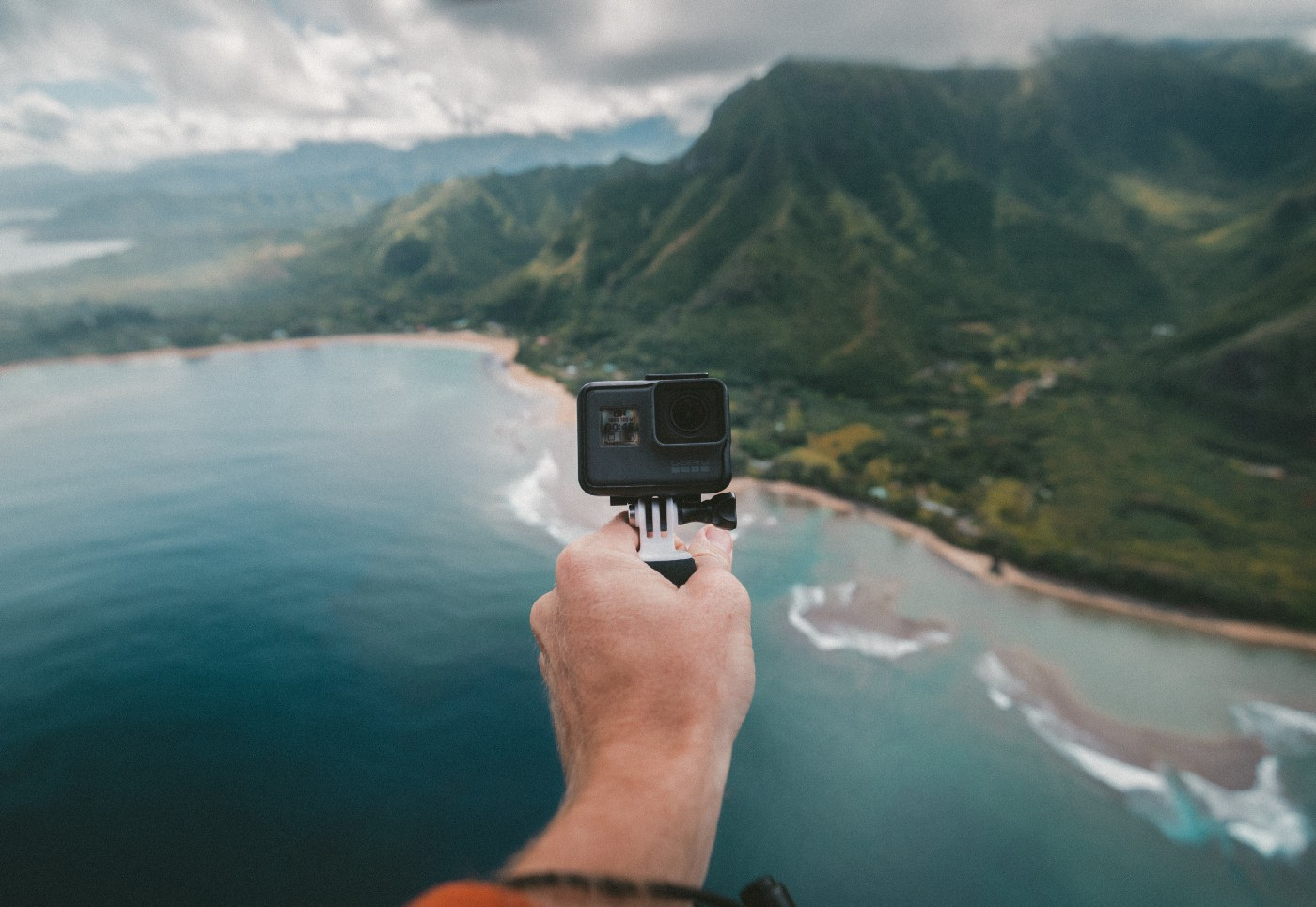 A focus shot of a person holding a GoPro camera with a wide landscape showing the sea and an island.