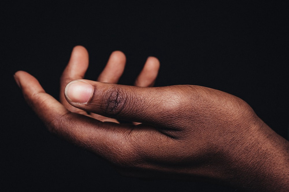 Black woman's empty palm against a black background.