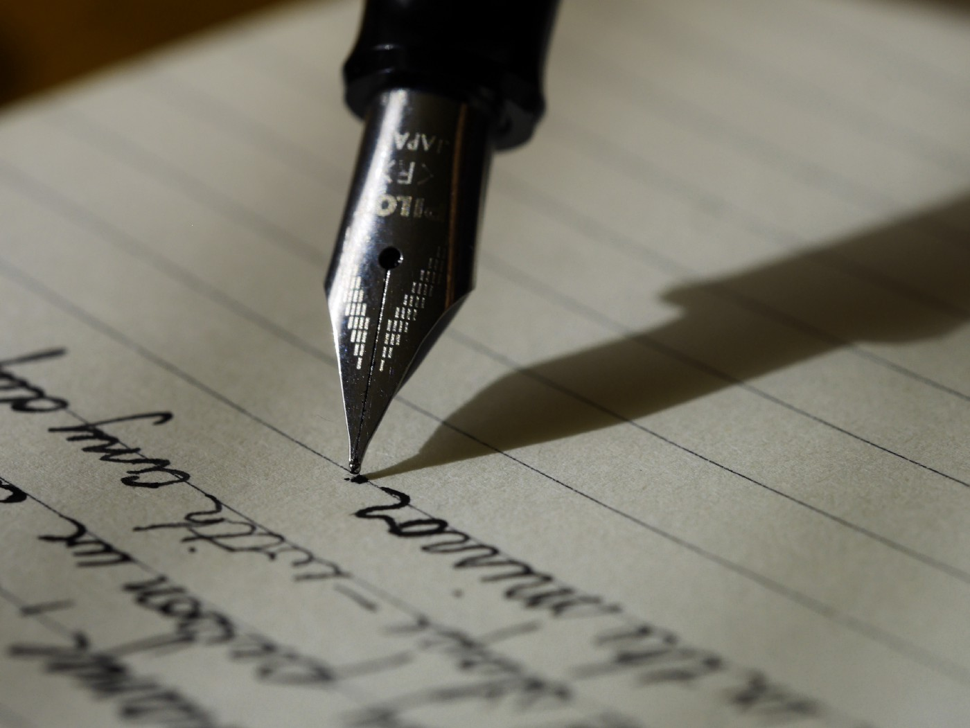 Fountain pen tip clearly visible against lined paper and the shadow clearly outlined as a reference to the human condition found written in our hearts.