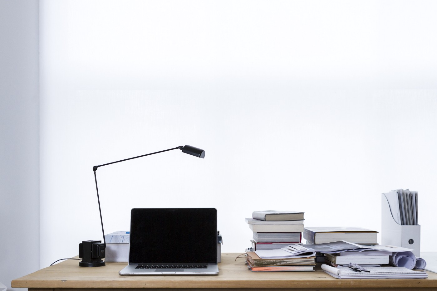 Laptop and modern lamp on a desk with minimalist background.