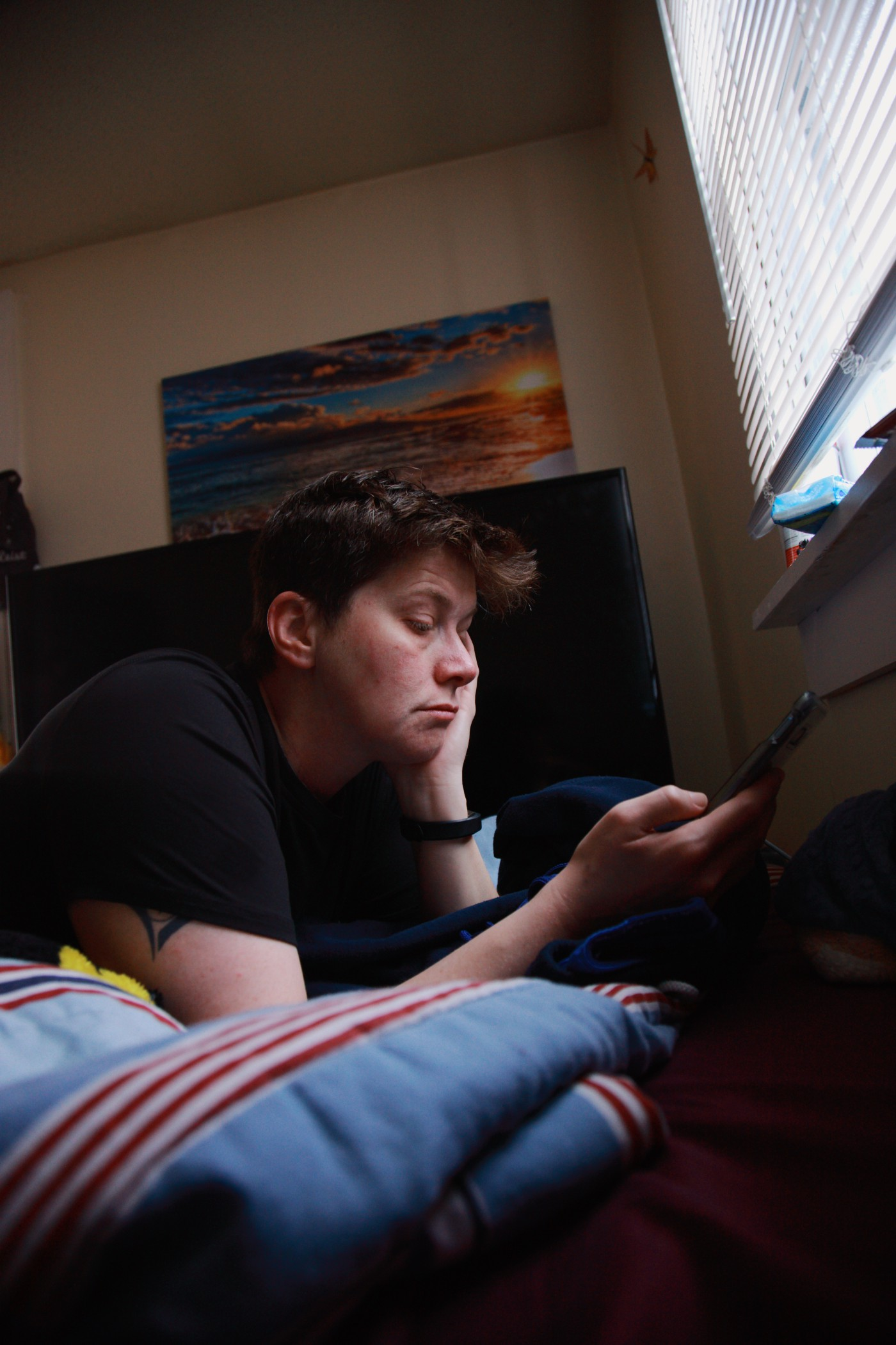 A person lays on their bed, staring at a mobile device, looking sullen.