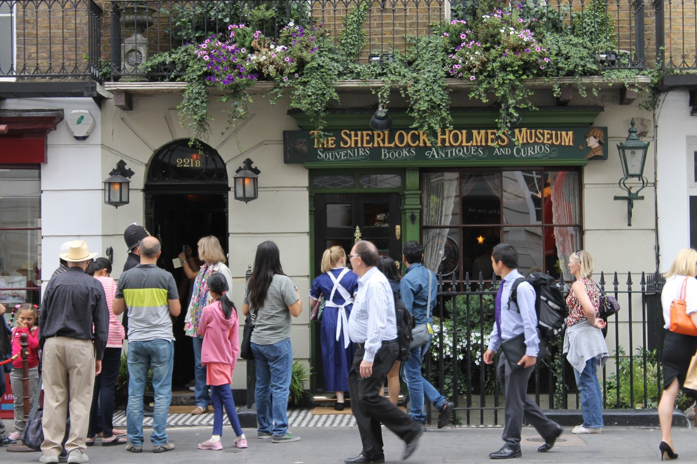 A picture of people walking along the street in front of the storefront for the Sherlock Holmes Museum in London.