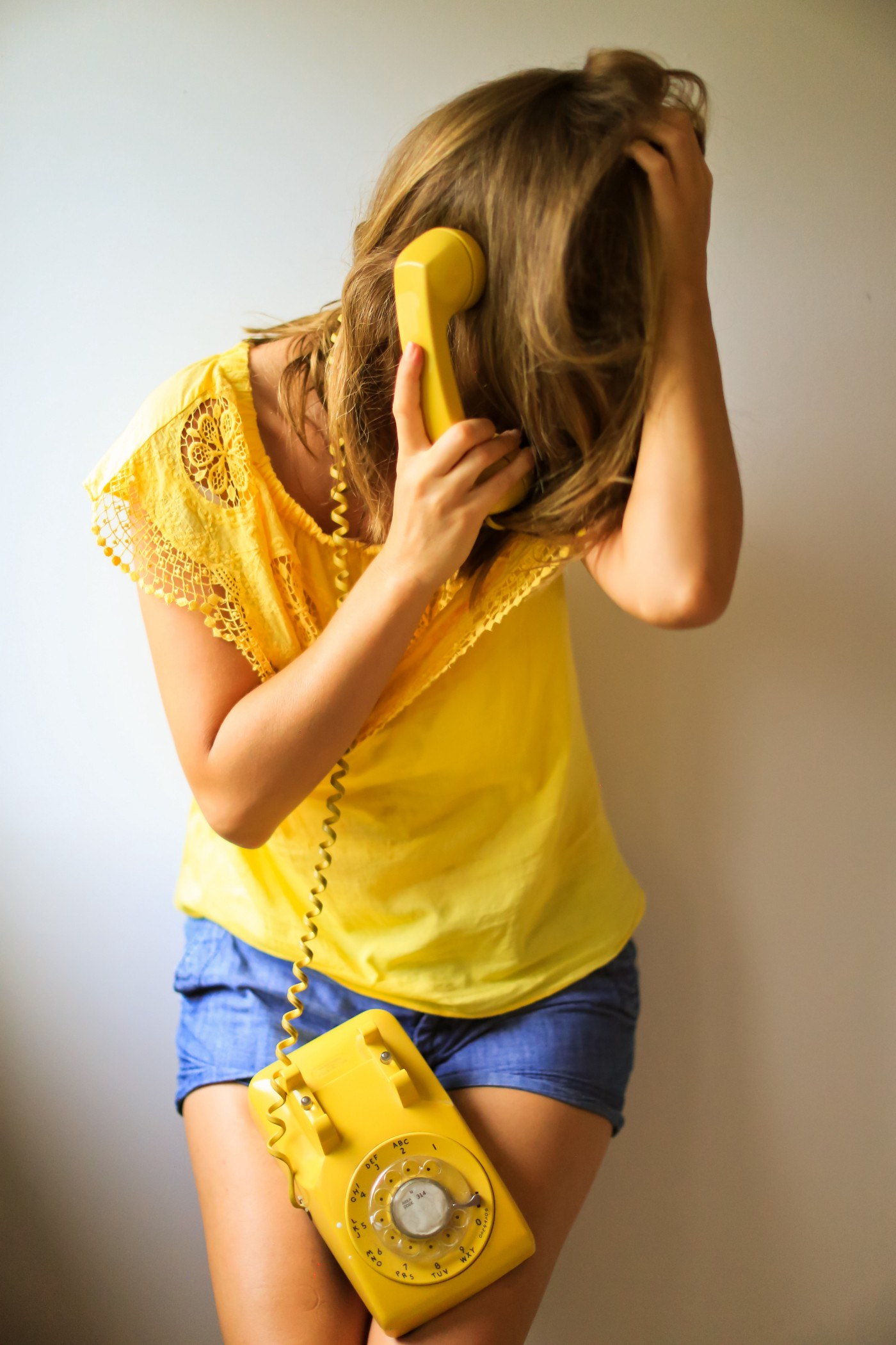a woman in yellow holds her head in frustration as she talks into a telephone