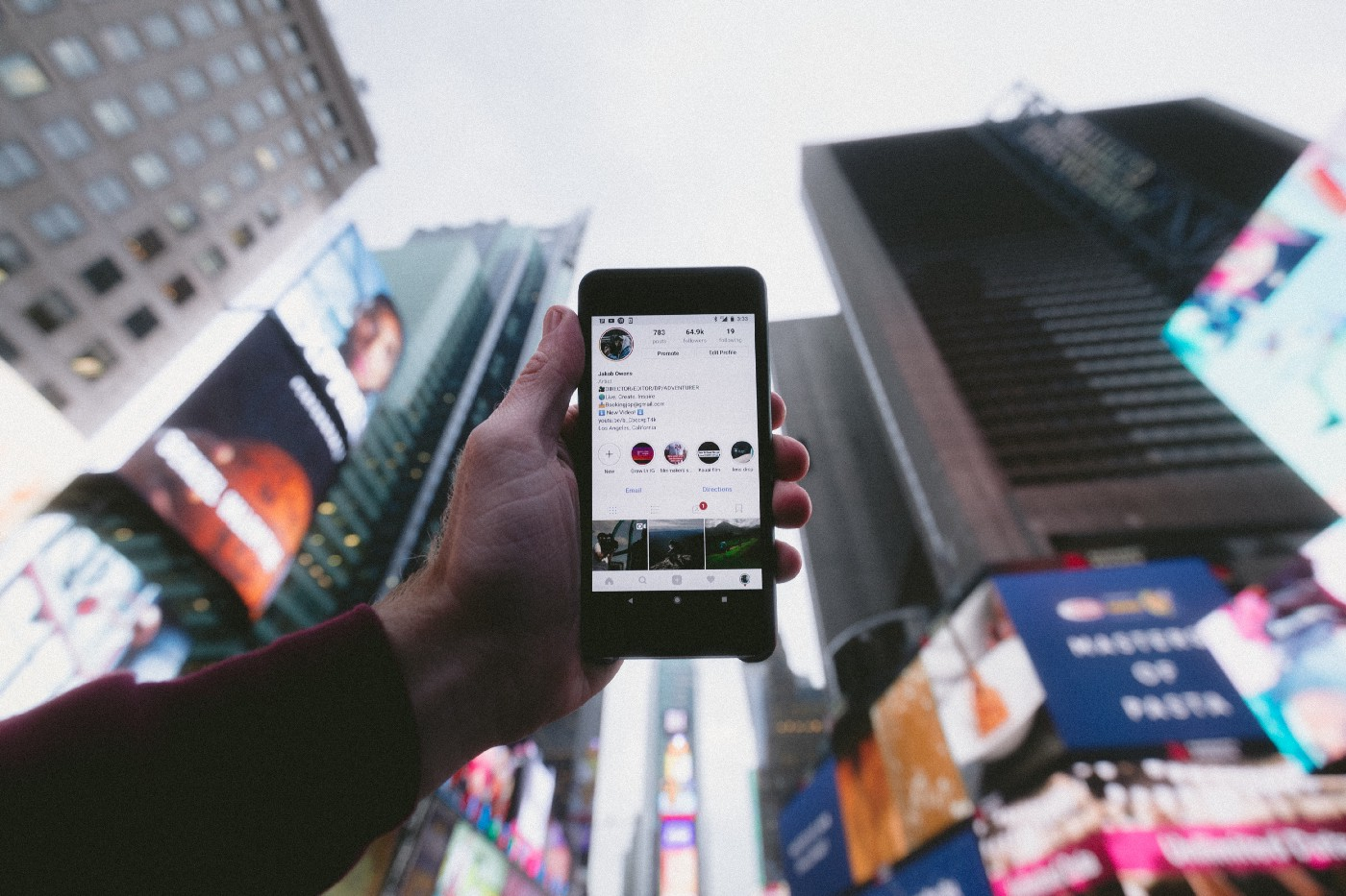 A person holds up a phone with high-rise buildings in the background.