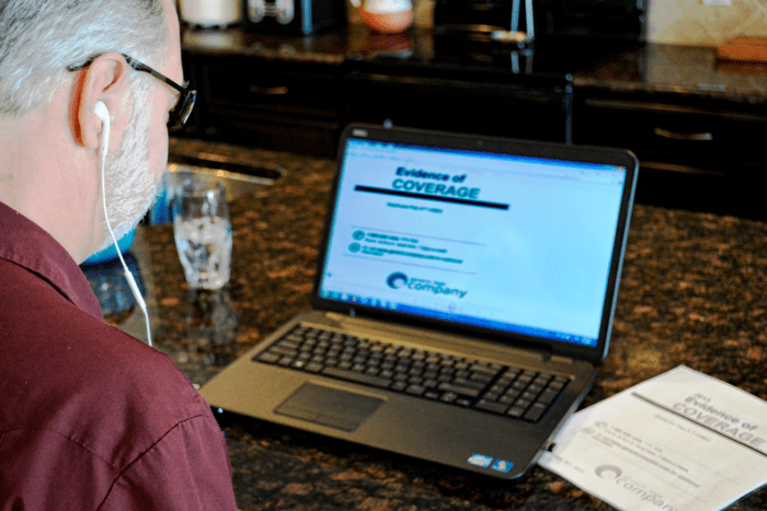 A man sitting in front of laptop computer listening to a 508 Compliant accessible PDF document with Screen Reading software.