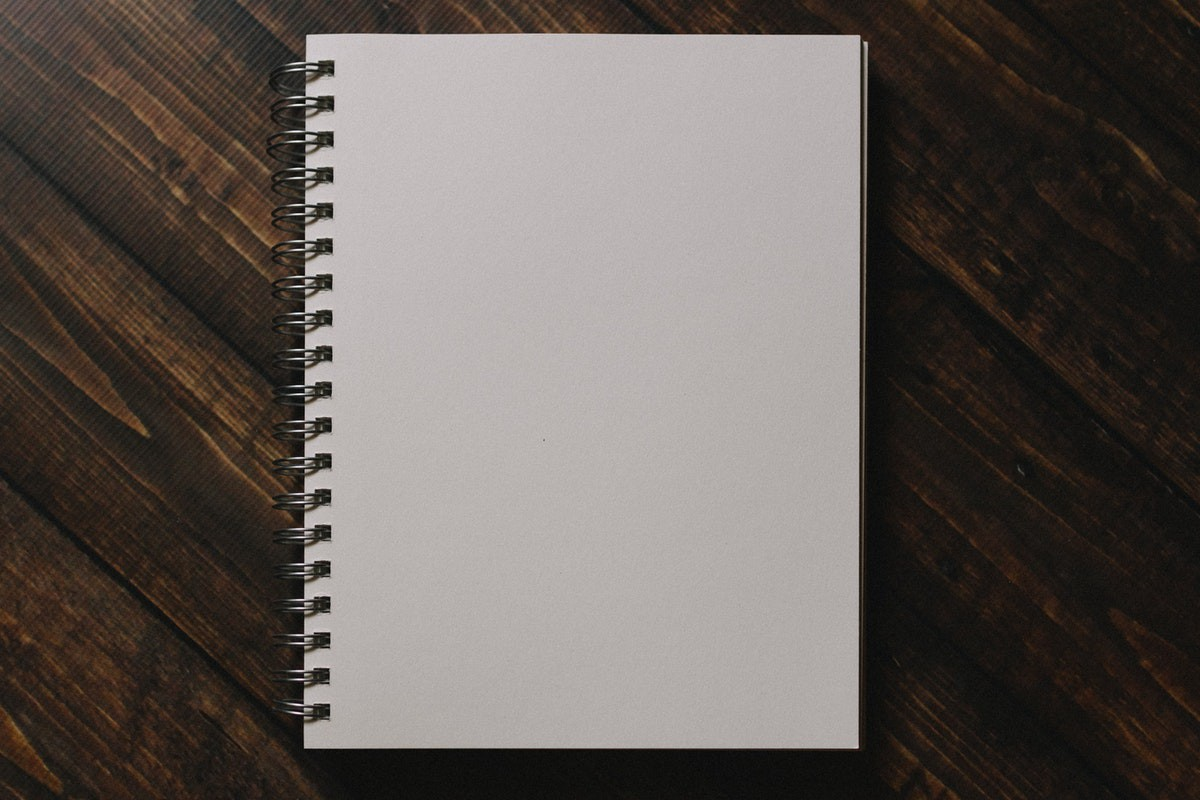 White notebook on wooden table.
