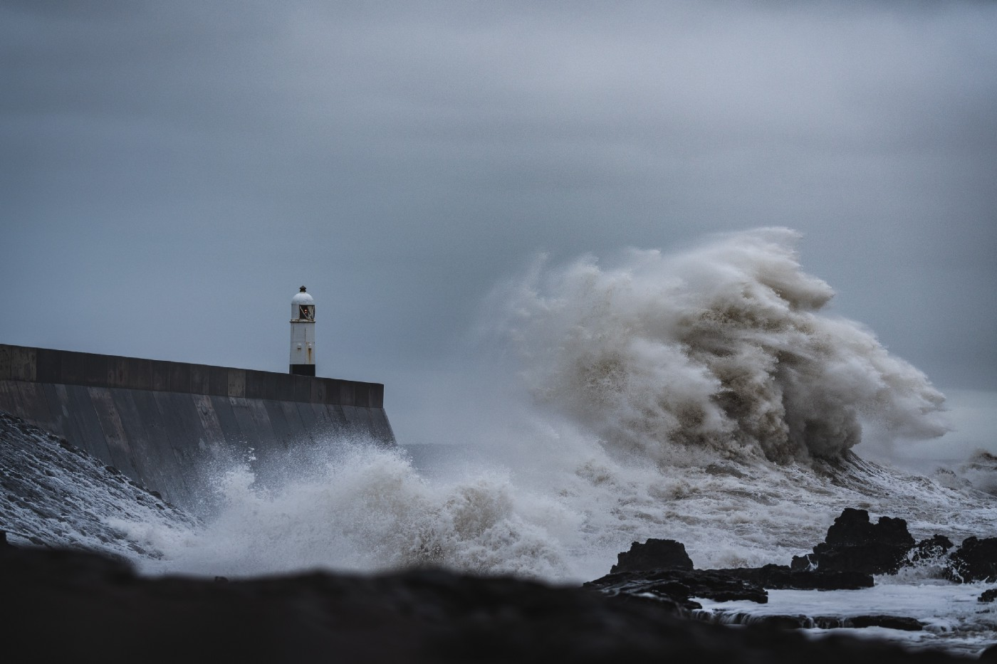 A huge wave crashes against a harbour wall with a small lighthouse
