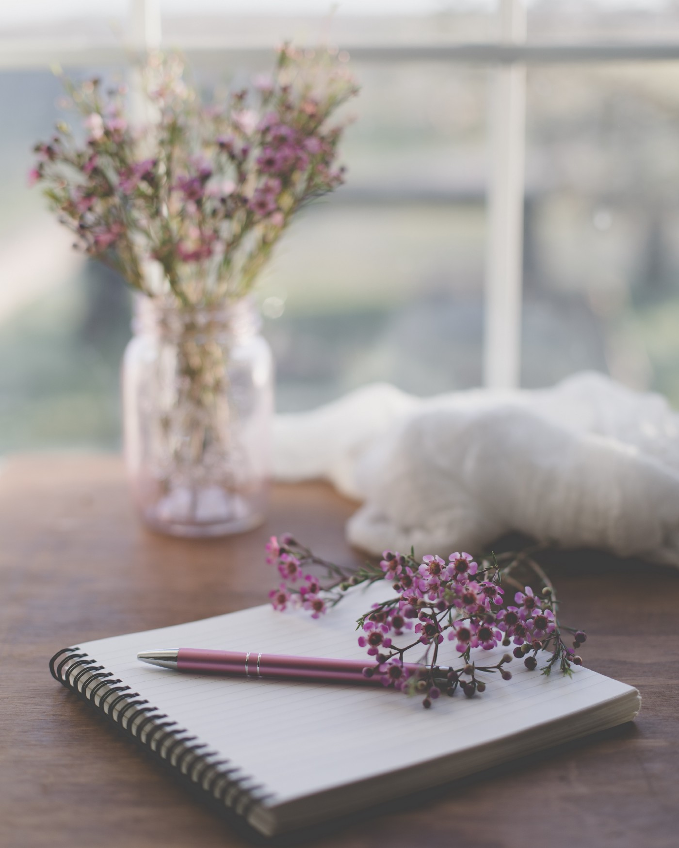 wire bound notebook open on a table with pink flowers on it and pink flowers in a vase