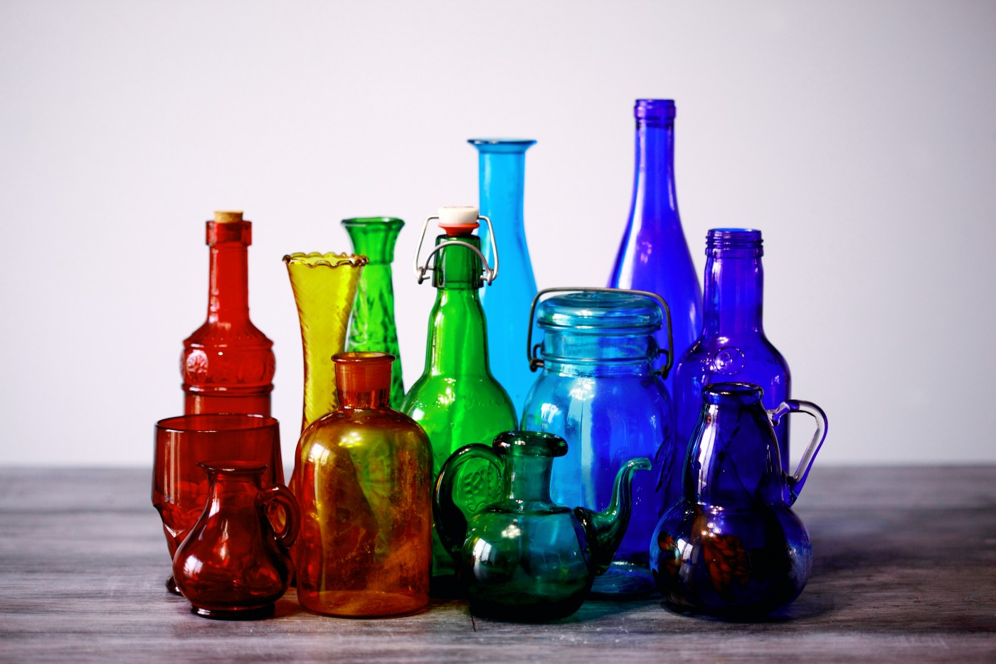 Glass bottles and jugs organized by color