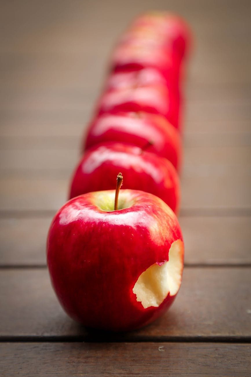 A row of red apples, with a bite taken from the closest