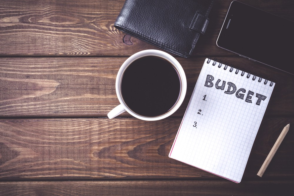 Budget planing concept. Top view of notepad with word Budget, mobile phone, cup of coffee, pouch on wooden background. Write idea success solution concept. Vintage toned picture. Copy space. Budgeting can help in reaching our saving goals.