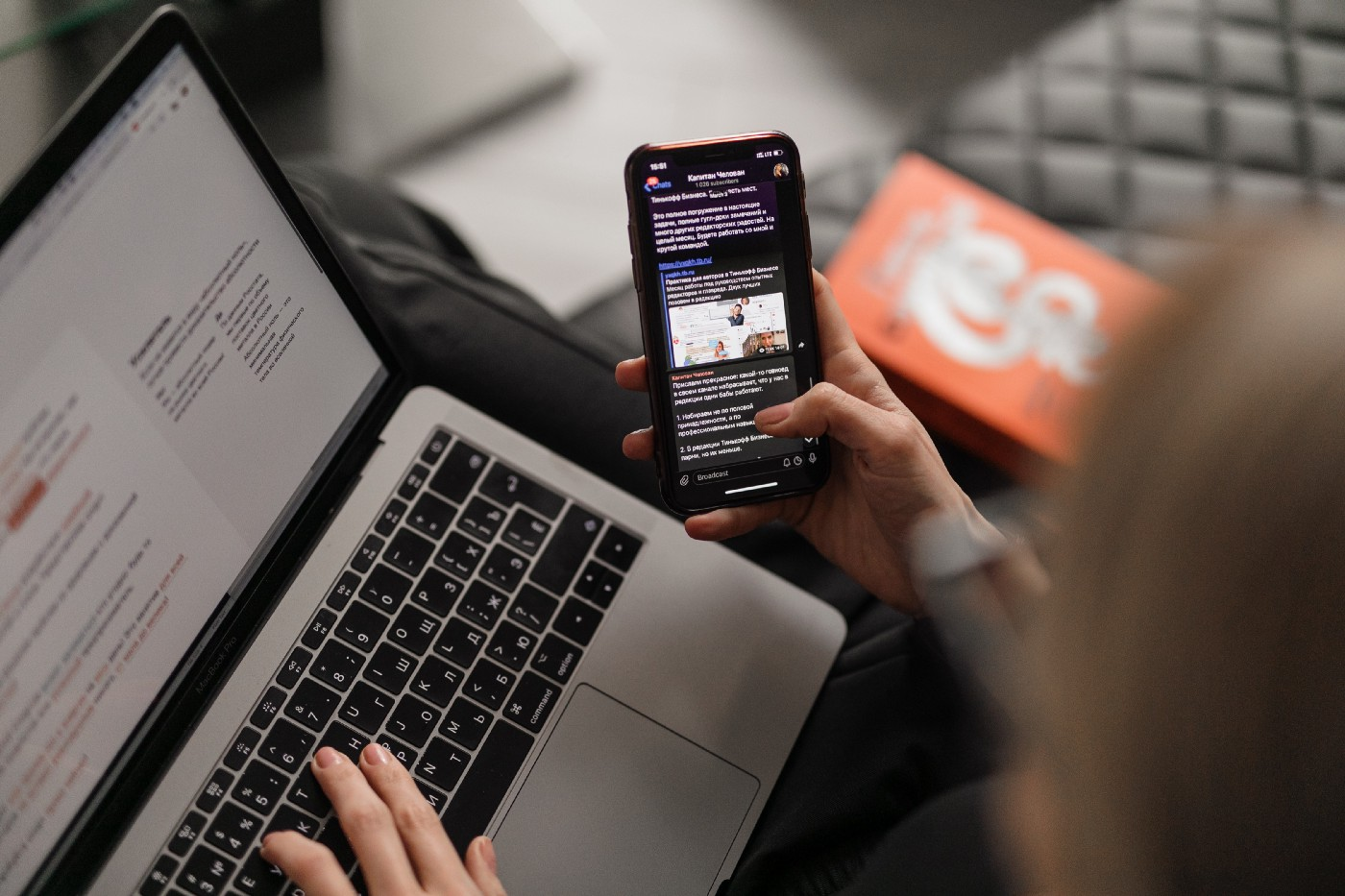 An overhead closeup of a caucasian woman sitting on a sofa at home. She is multitasking: scrolling her black smartphone in her right hand and resting her left hand on her laptop keyboard. This Will Make People Want Your Digital Product—Food for thought for all online entrepreneurs and business owners trying to sell your digital product.