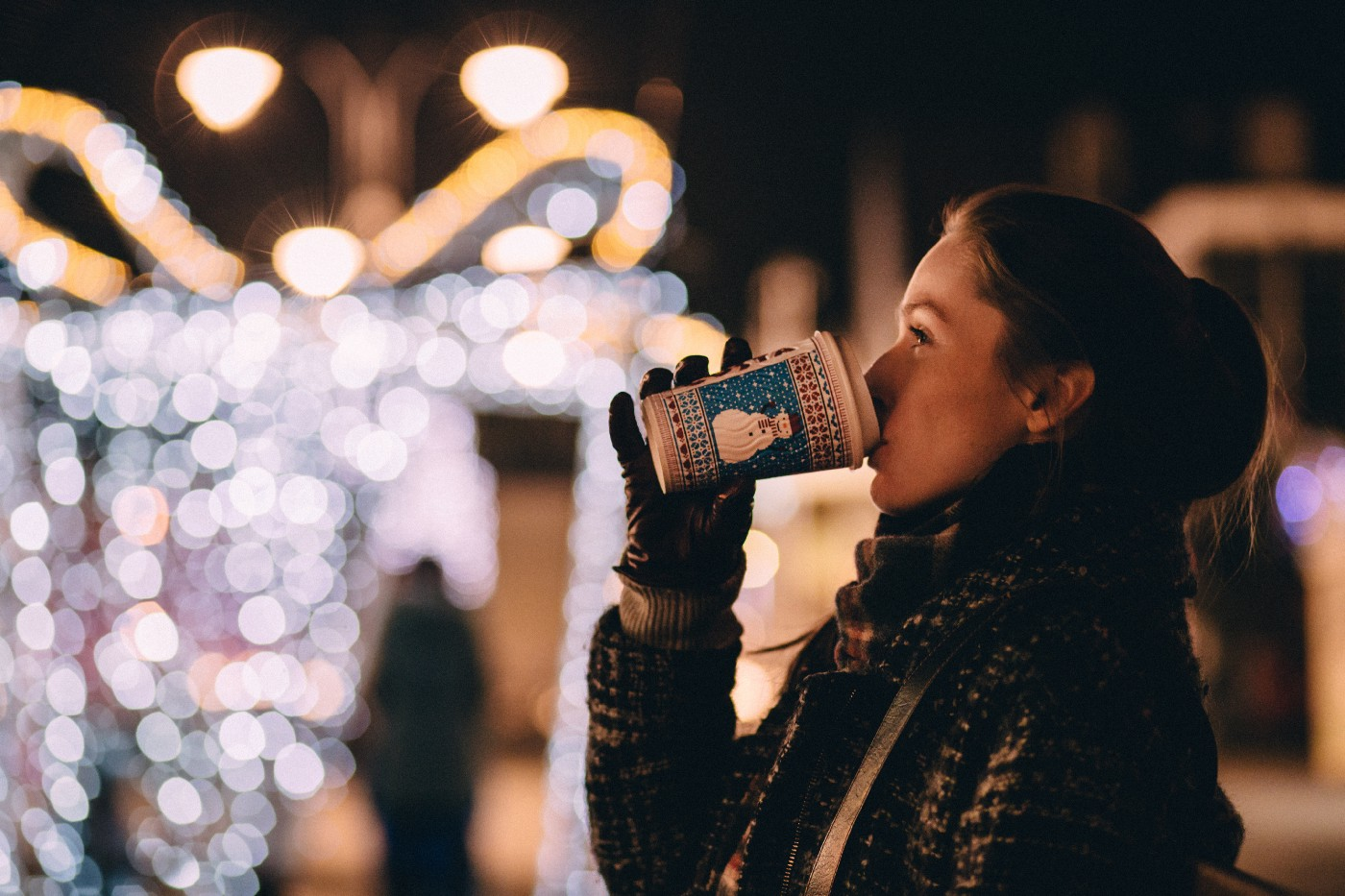 Woman drinking a coffee in a Christmas design cup with Christmas lights in background.