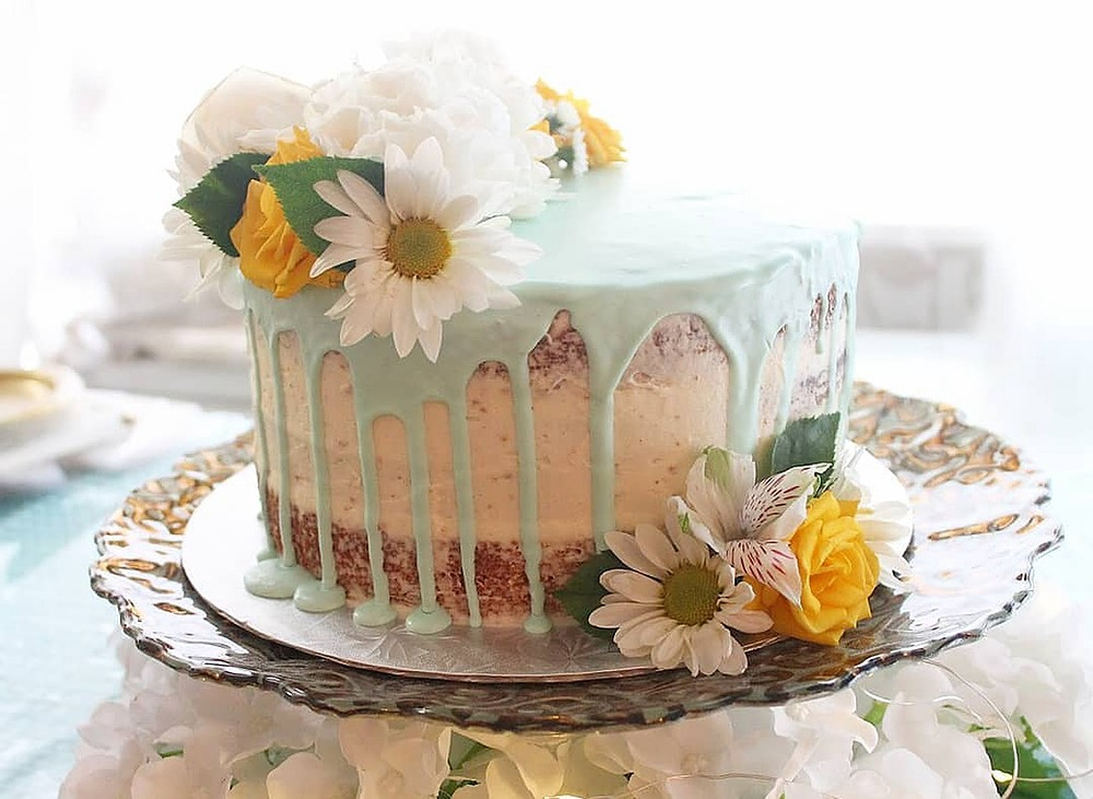 A cake with green frosting and white sunflowers on top