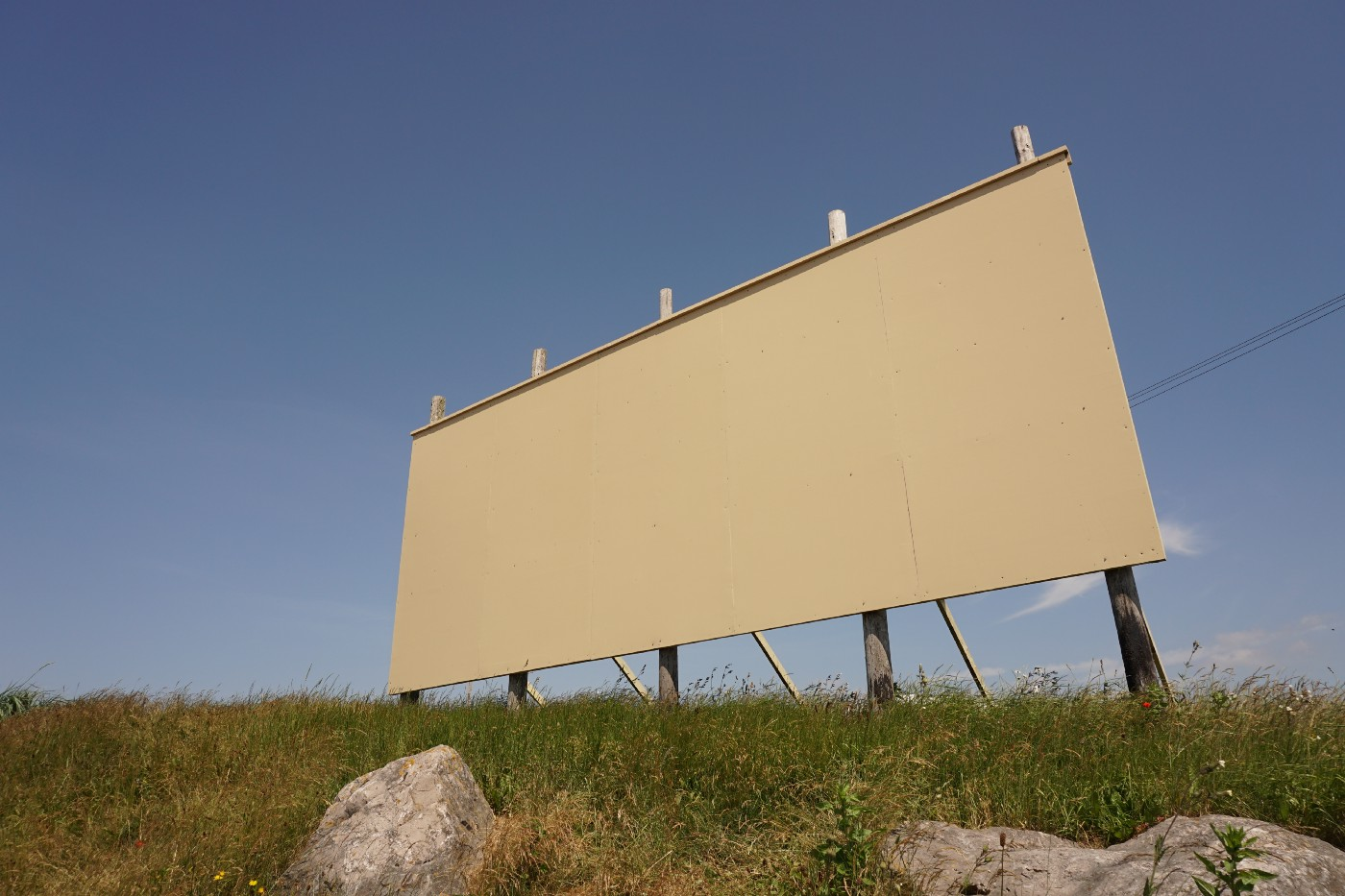 A blank, white billboard on the side of a deserted highway with some dry rocks and sun damaged grass.