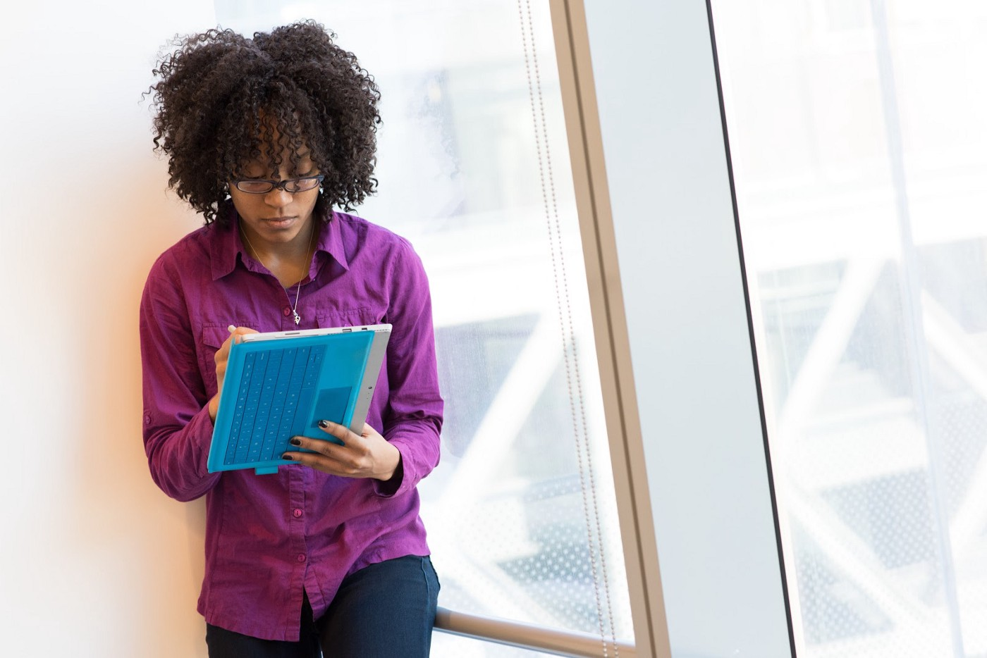 Black woman with curly hair wearing glasses and a purple button down shirt stands in front of a wall writing on a tab